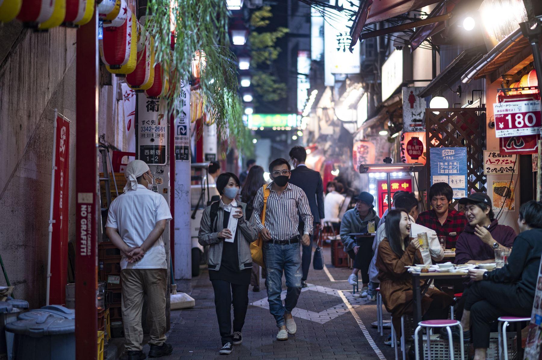 Personas que usan máscaras faciales como medida preventiva ante el coronavirus visitan el área de restaurantes del callejón Omoide Yokocho en el distrito Shinjuku de Tokio. Foto: AFP