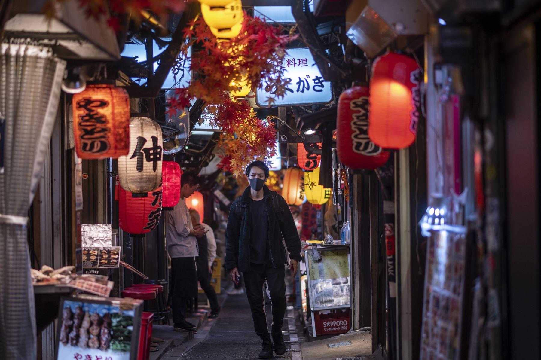 Un hombre que llevaba una mascarilla como medida preventiva ante el coronavirus camina por el área de restaurantes del callejón Omoide Yokocho en el distrito Shinjuku de Tokio. Foto: AFP