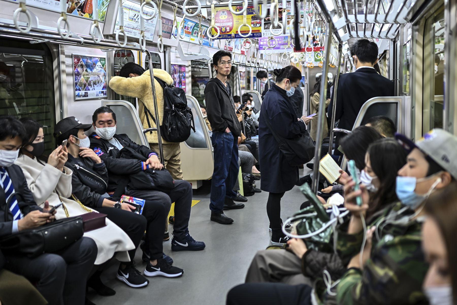 Las personas que usan mascarillas como medida preventiva ante el coronavirus, viajan a última hora de la noche en Tokio. Foto: AFP