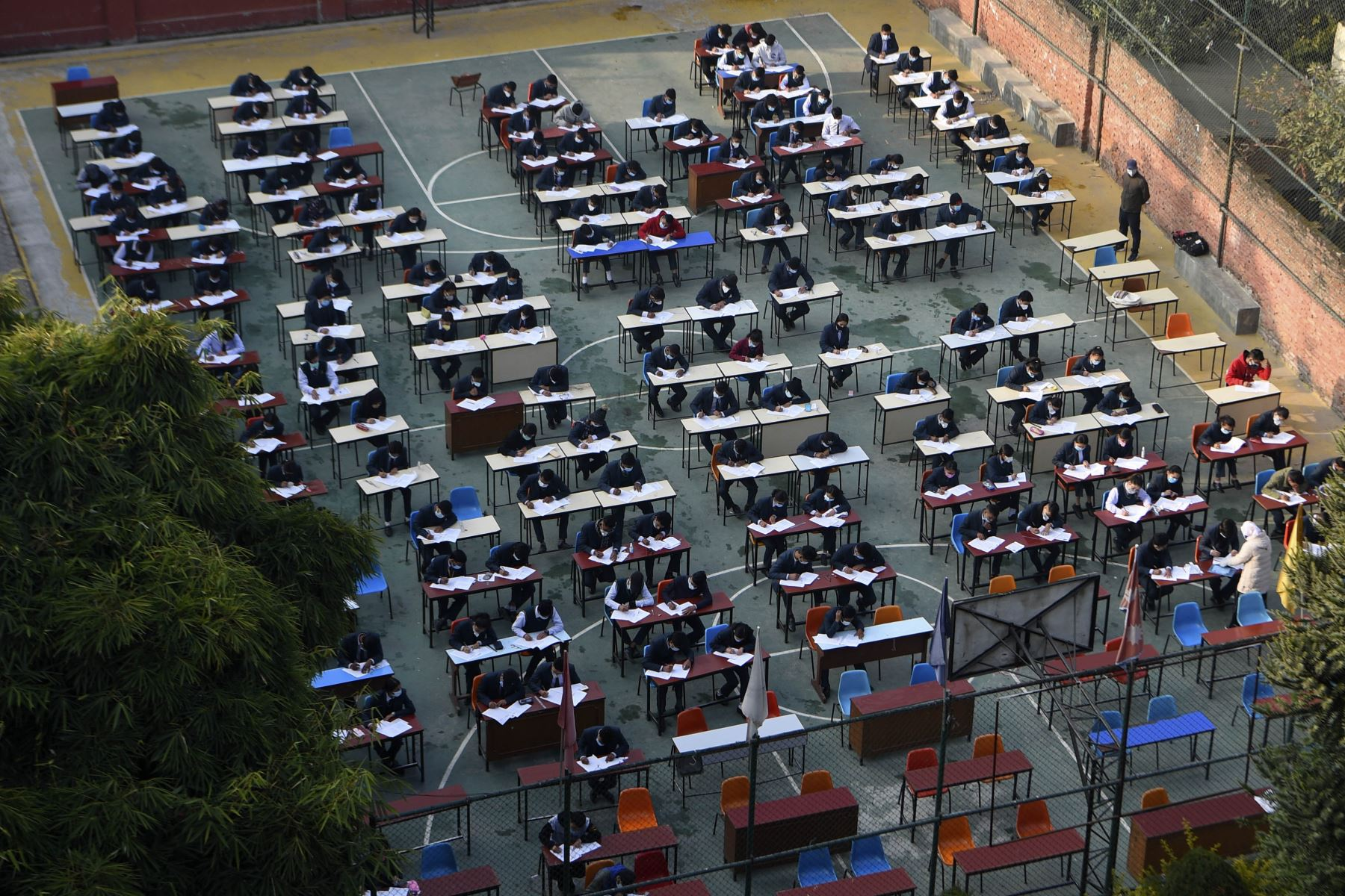 Estudiantes que usan mascarillas rinden el examen en el patio de la escuela en medio de la pandemia del coronavirus Covid-19 en Katmandú. Foto: AFP