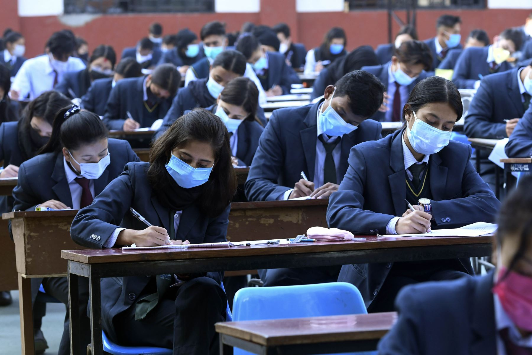 Estudiantes que usan mascarillas rinden el examen en el patio de la escuela en medio de la pandemia del Covid-19 en Katmandú. Foto: AFP