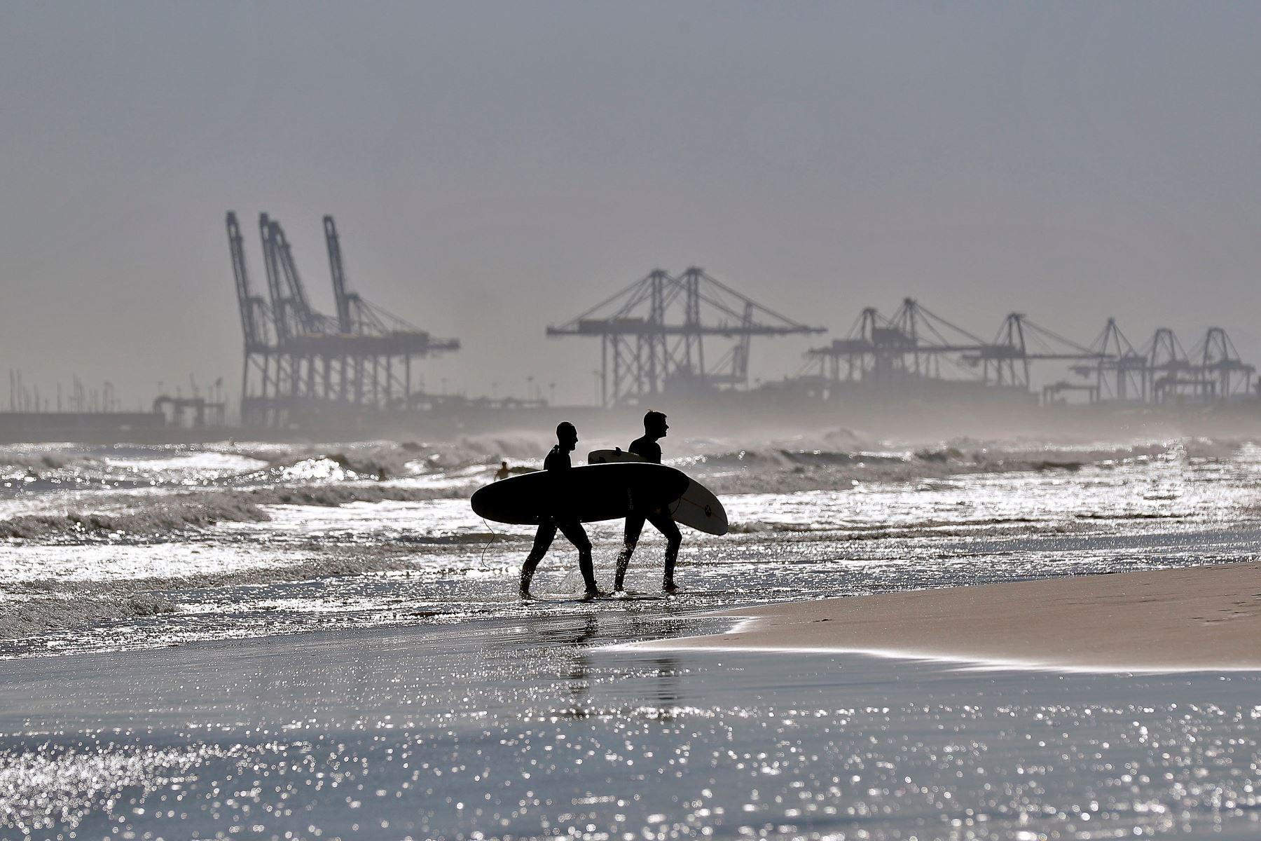 Dos surfistas en la playa de La Malvarrosa de Valencia donde las olas y el cielo despejado han animado a muchos practicar este deporte. Foto: EFE