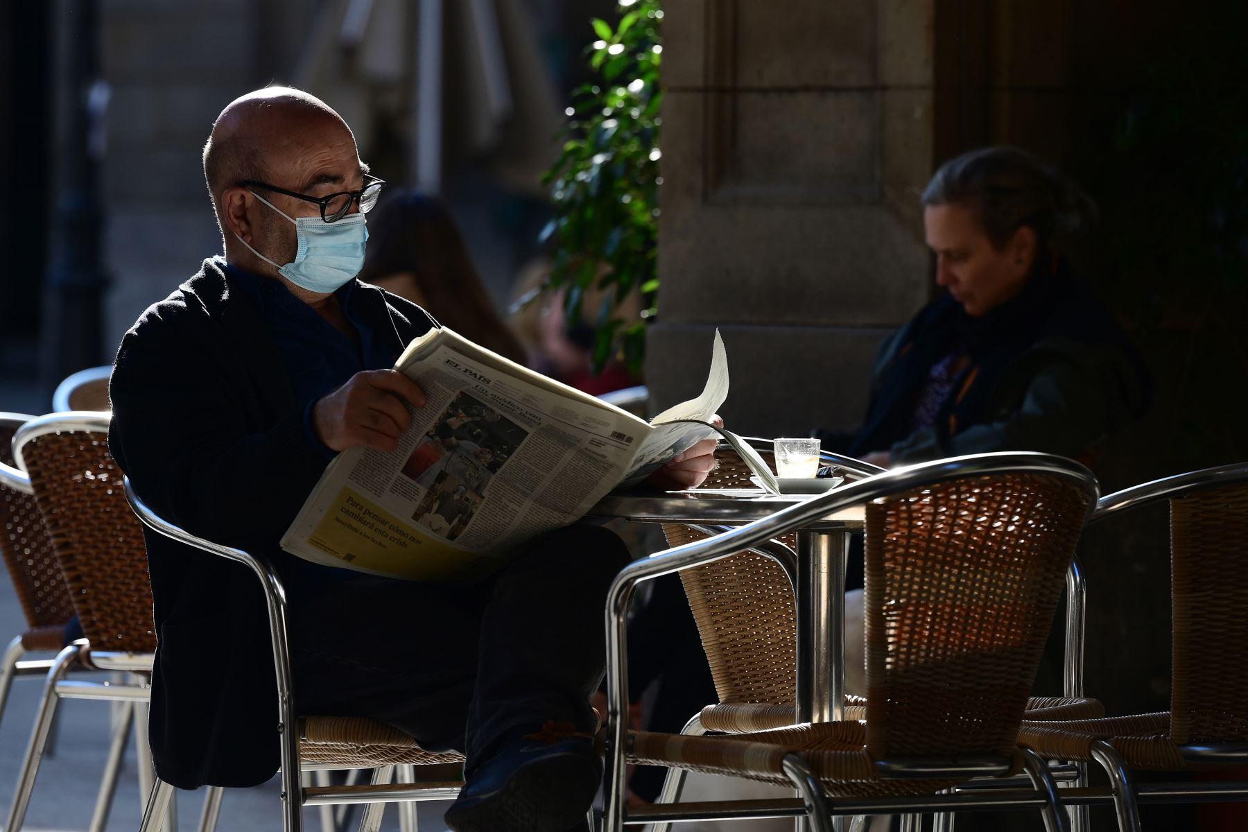Un hombre lee un periódico en un restaurante de Barcelona mientras se permitía la reapertura de bares, restaurantes y cines en la región nororiental española de Cataluña. Foto: AFP