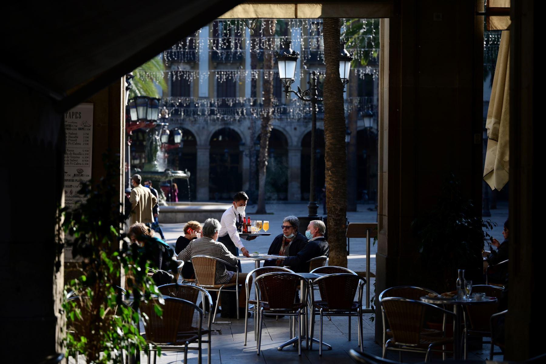 Un camarero atiende a los clientes en un restaurante de Barcelona cuando se permitió la reapertura de bares, restaurantes y cines en la región nororiental española de Cataluña. Foto: AFP