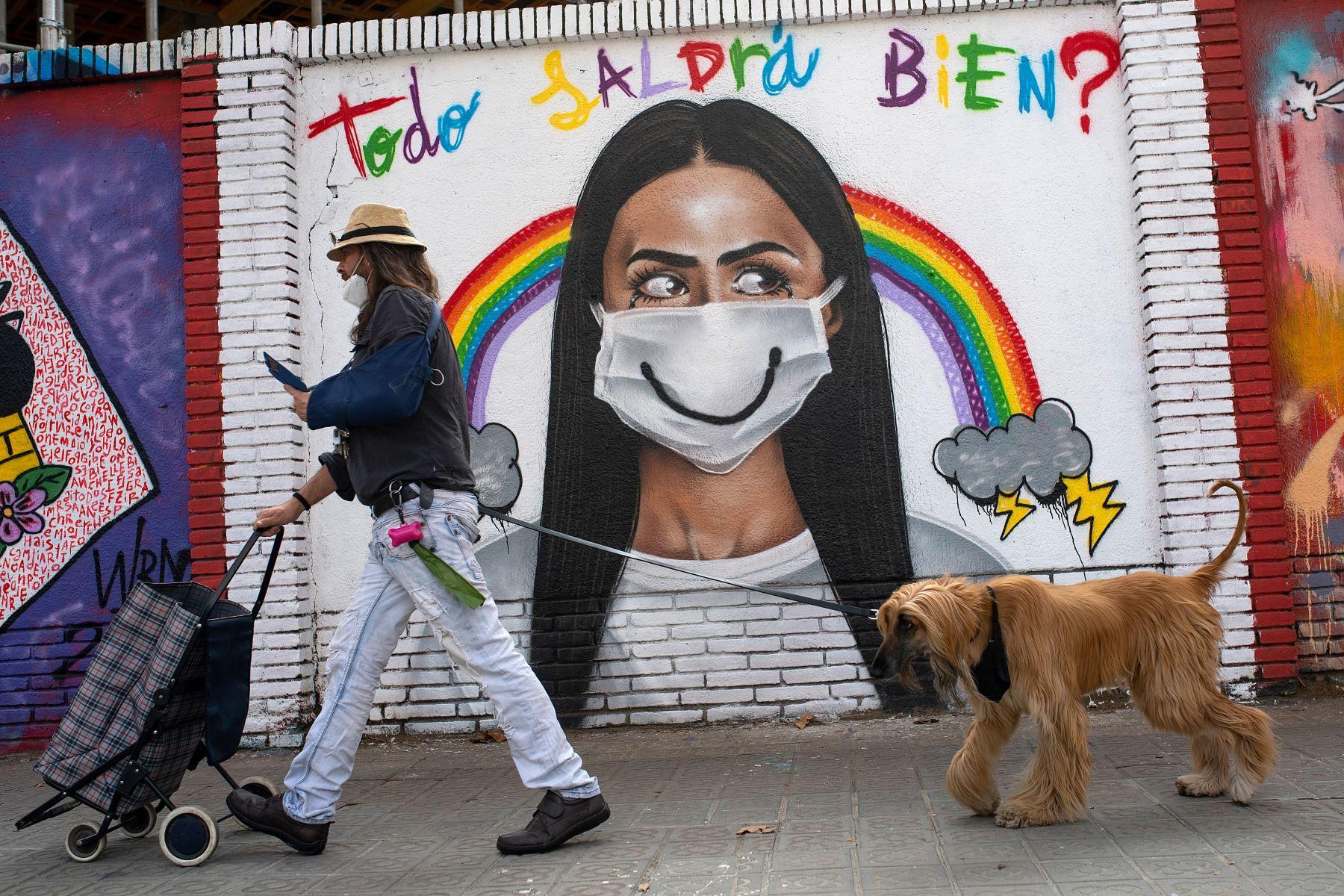 Un ciudadano que pasea a su mascota pasa junto a un mural en el centro de Barcelona. Foto: AFP