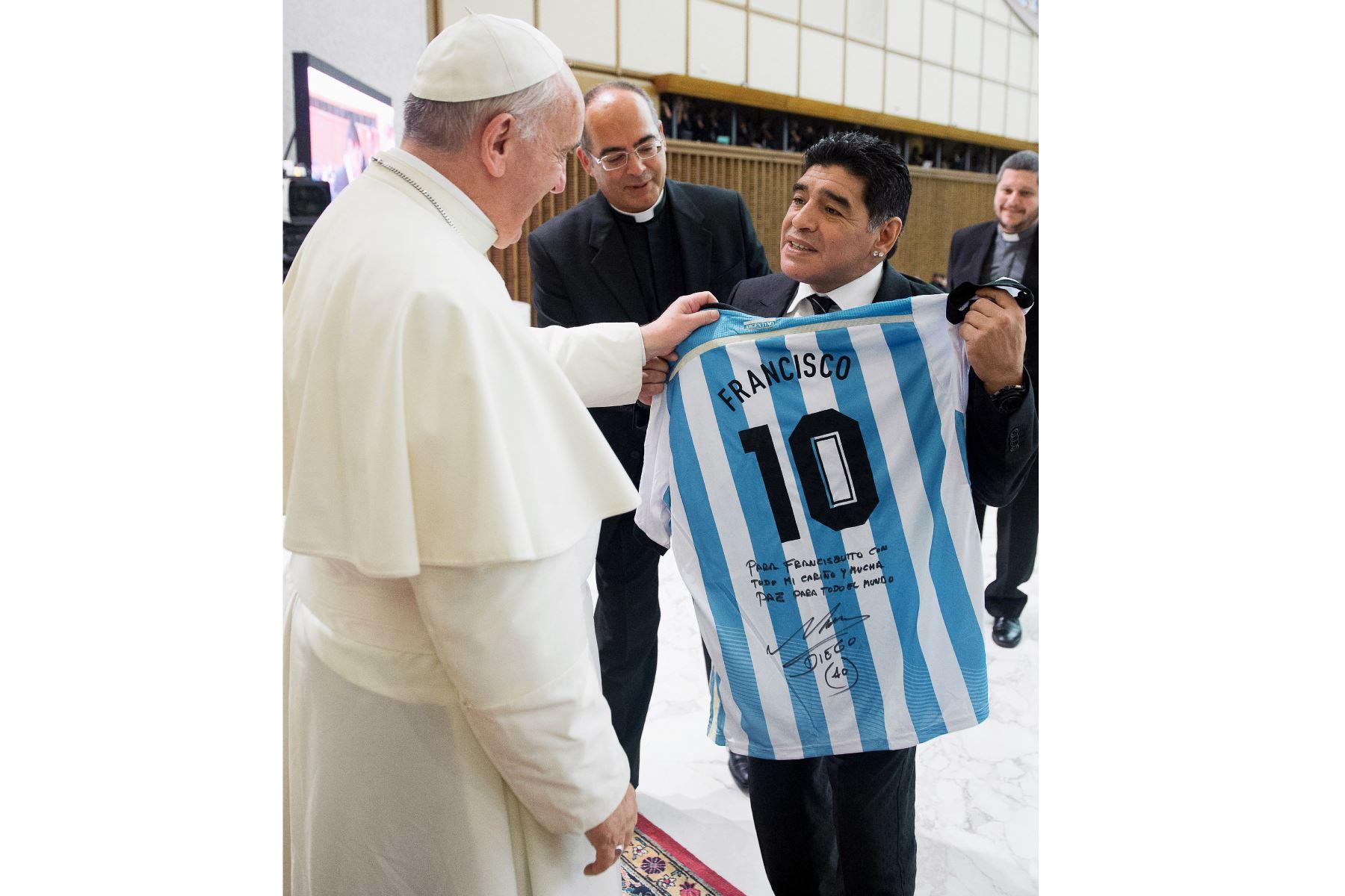 Esta fotografía tomada y publicada el 1 de septiembre de 2014 por el Osservatore Romano, la oficina de prensa del Vaticano, muestra al exfutbolista argentino Diego Armando Maradona presentando una camiseta personalizada de Argentina al Papa Francisco. Foto: AFP