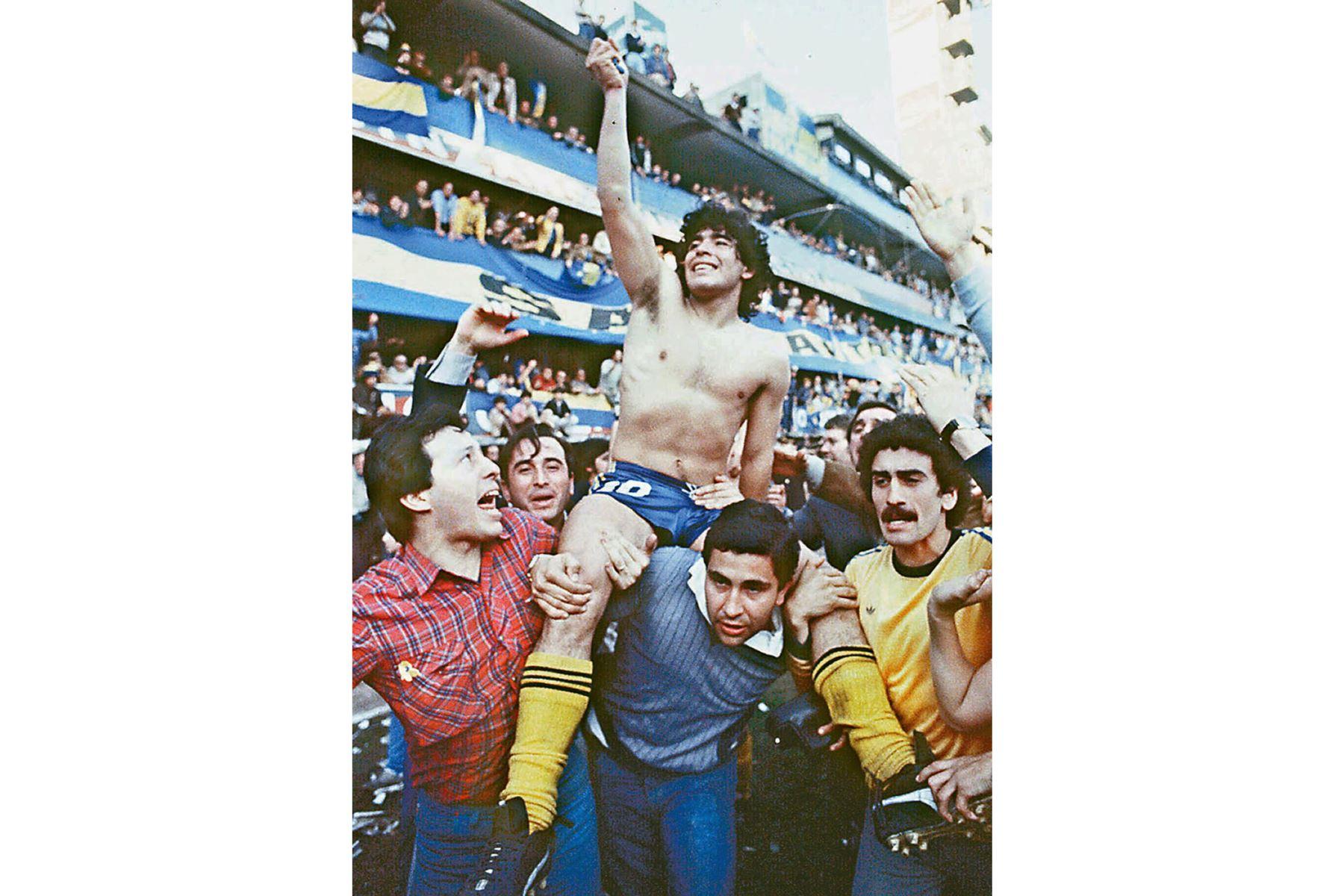 Esta imagen de 1981 muestra al astro del fútbol argentino Diego Armando Maradona, siendo llevado por fanáticos después de ganar el Campeonato local de 1981 con Boca Juniors en el estadio La Bombonera de Buenos Aires. Foto: AFP