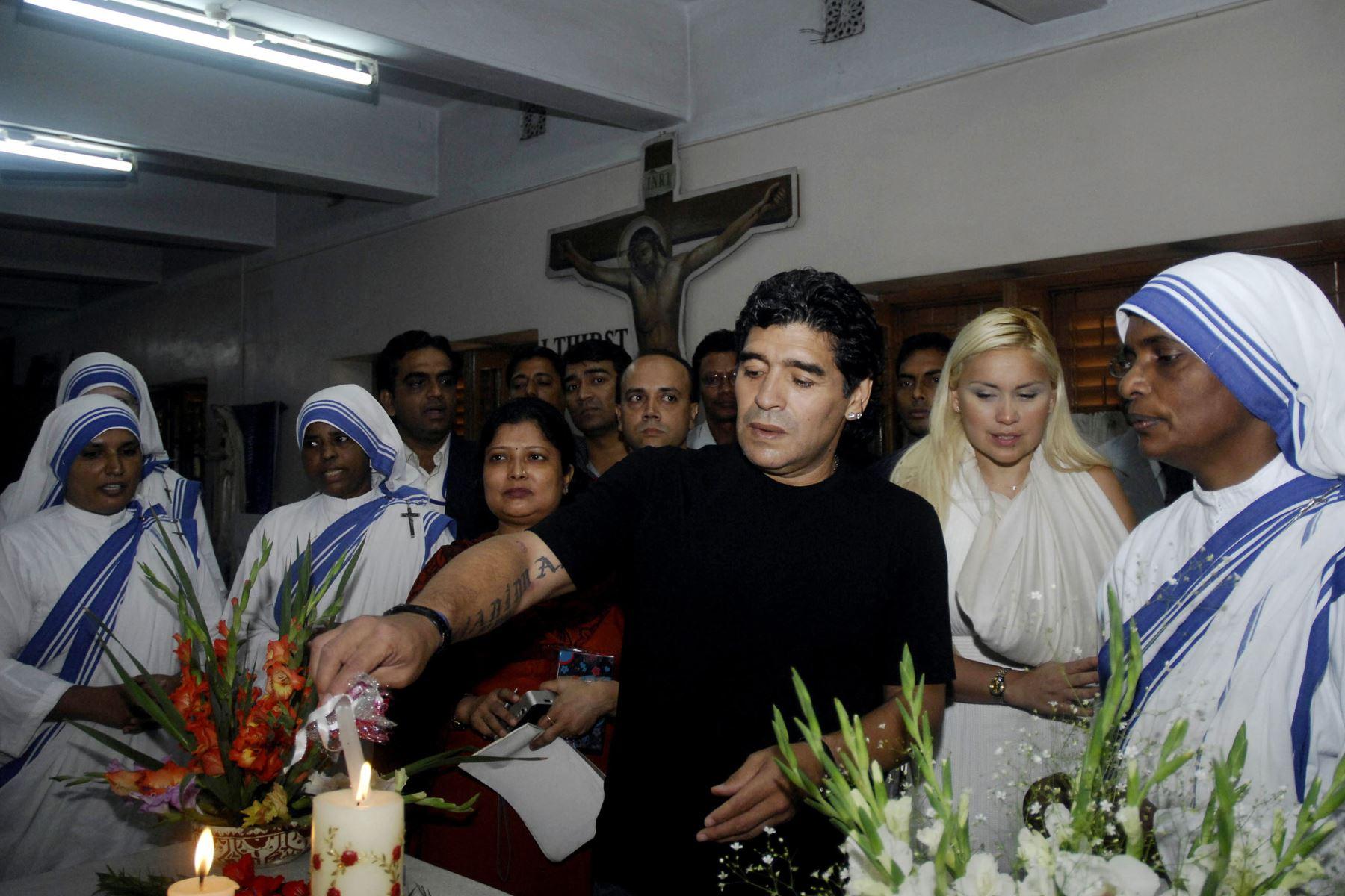 El entrenador de la selección nacional de fútbol de Argentina y ex estrella del fútbol Diego Armando Maradona enciende una vela mientras su novia Verónica observa junto con las monjas de la orden de las Misioneras de la Caridad de la Madre Teresa en Calcuta, el 7 de diciembre de 2008, en la India. Foto: AFP