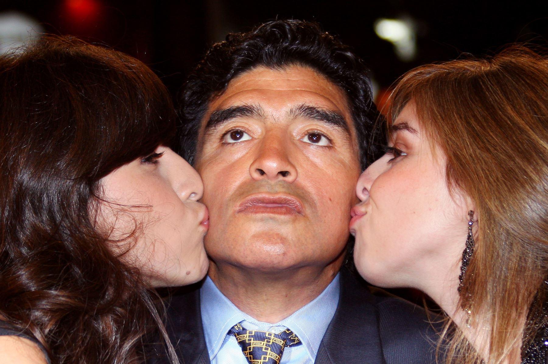En esta foto de archivo tomada el 20 de mayo de 2008, el ex jugador de fútbol argentino Diego Maradona es es besado por sus hijas Giannina y Dalma cuando llega para asistir a la proyección del documental del director serbio Emir Kusturica