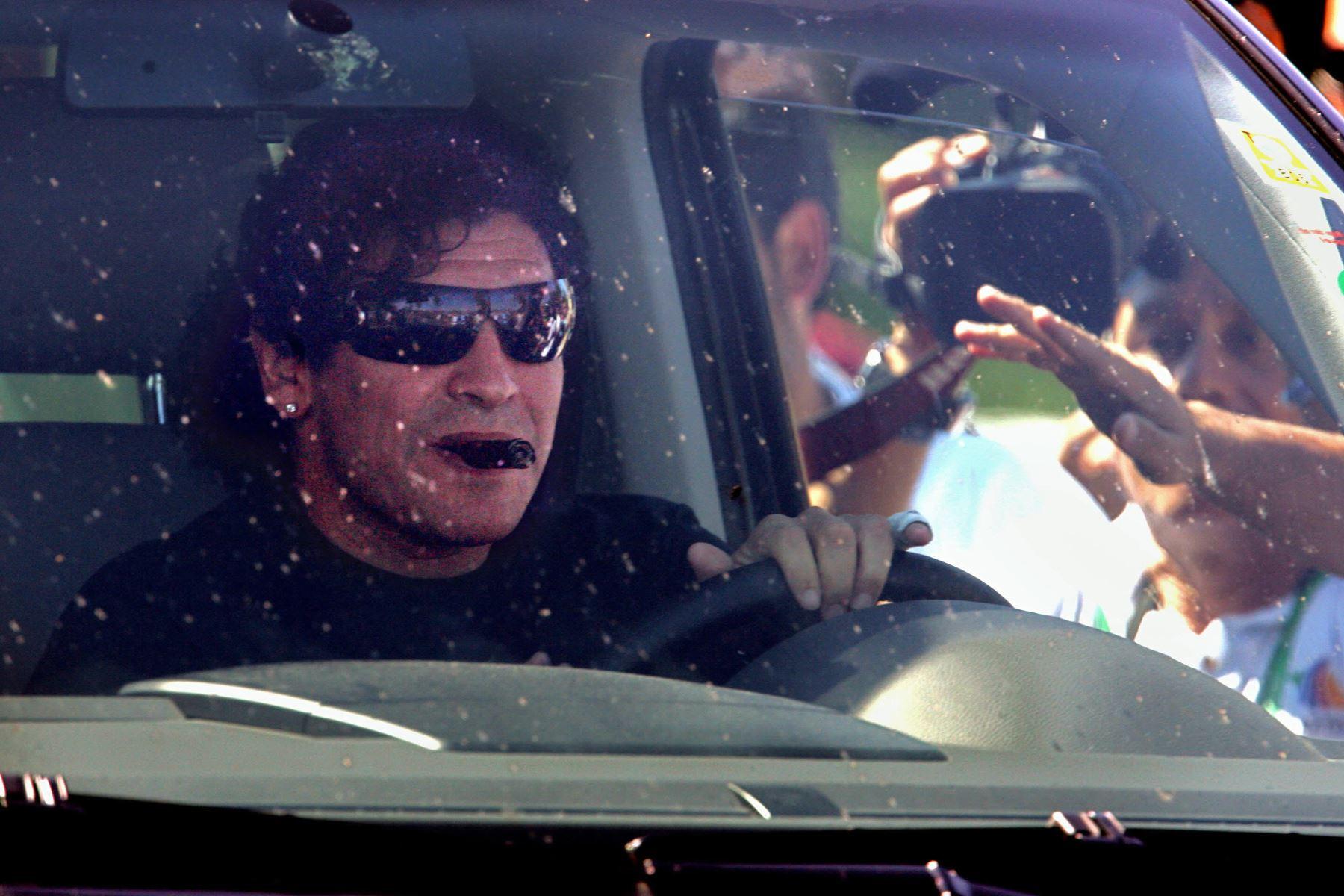 En esta foto de archivo tomada el 12 de junio de 2006, la gente saluda al astro del fútbol argentino Diego Maradona mientras se transporta en automóvil para salir del Hotel HerzogsPark en Herzogenaurach, en el sur de Alemania, durante el Mundial de Fútbol de Alemania 2006. Foto: AFP