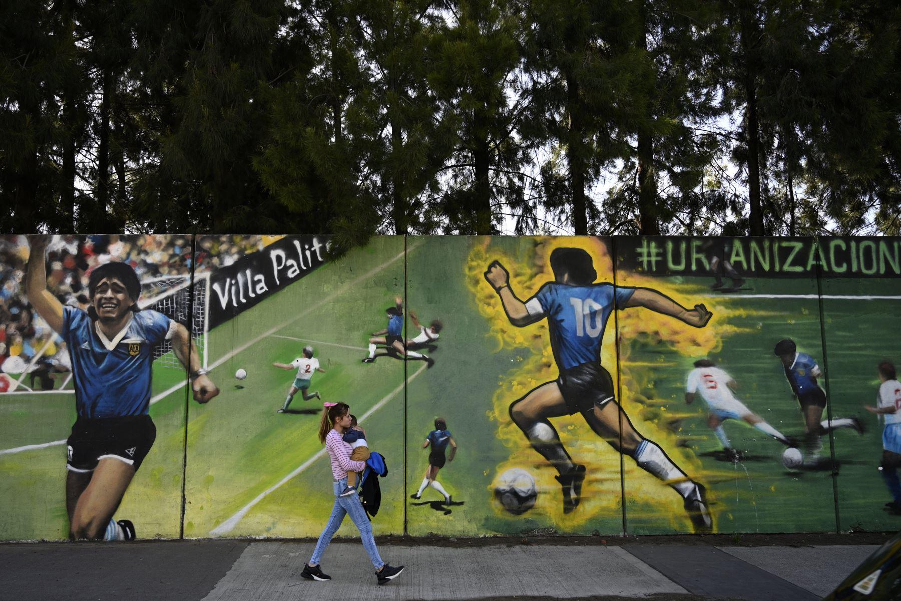 """Una mujer pasa junto a un mural del artista callejero """"Uasen"""" que representa al ex astro del fútbol argentino Diego Maradona, actual entrenador de la selección Gimnasia y Esgrima La Plata, anotando el segundo gol en el partido de la Copa Mundial de la FIFA México 86 contra Inglaterra, en Villa Palito. Foto: AFP"""