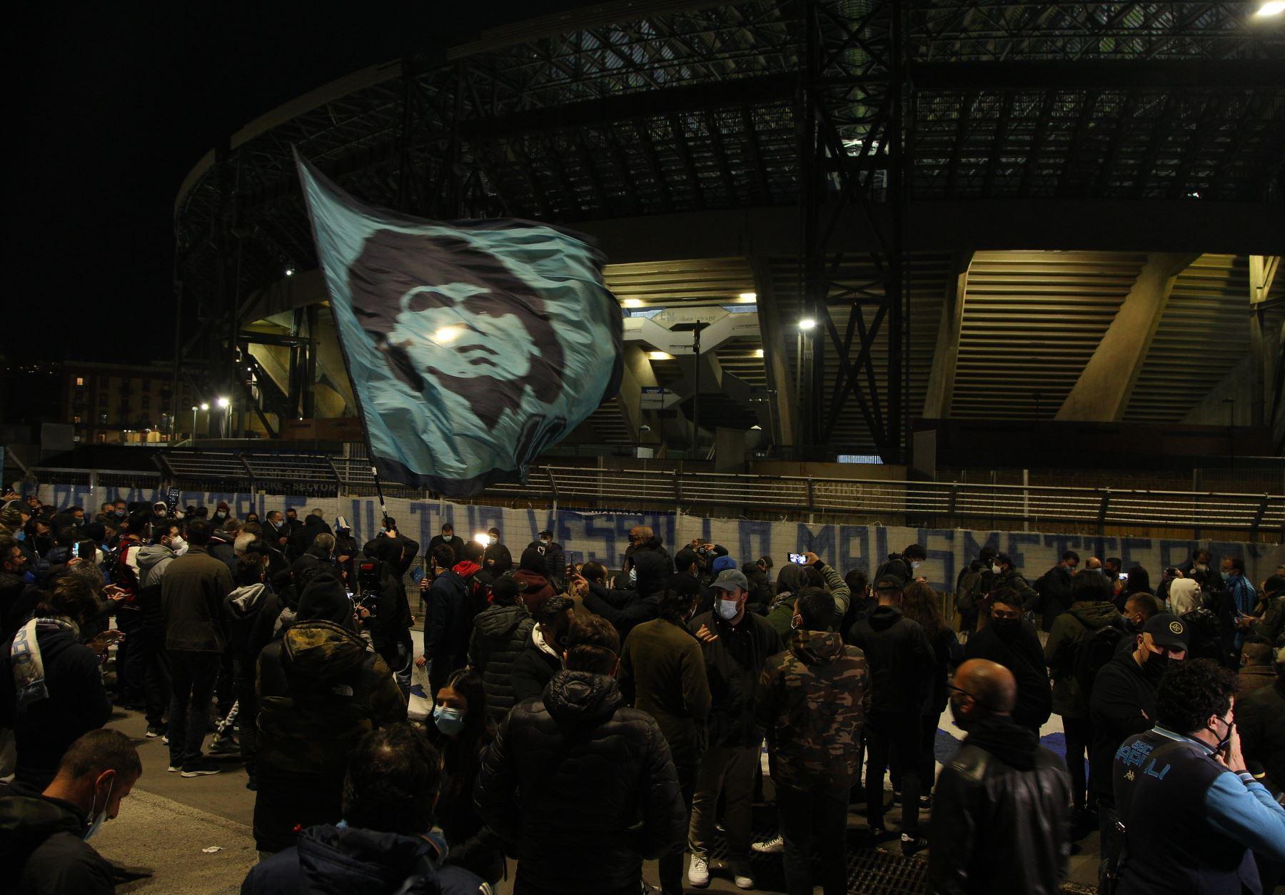 La gente se reúne en la entrada principal del estadio San Paolo en Nápoles, agitando una bandera ante la efigie de la leyenda del fútbol argentino Diego Maradona, para llorar después del anuncio de la muerte de Maradona. Foto: AFP