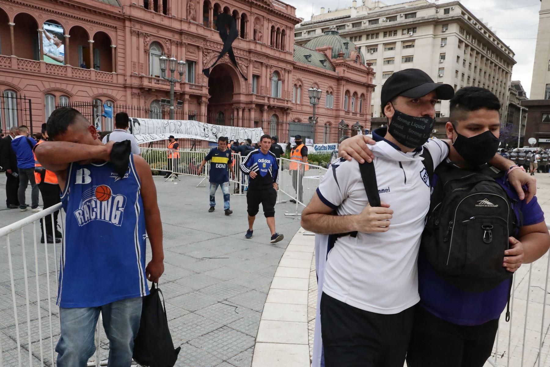 La gente reacciona al salir  del palacio presidencial en Buenos Aires después de rendir homenaje al féretro de la leyenda del fútbol Diego Maradona. Foto:AFP
