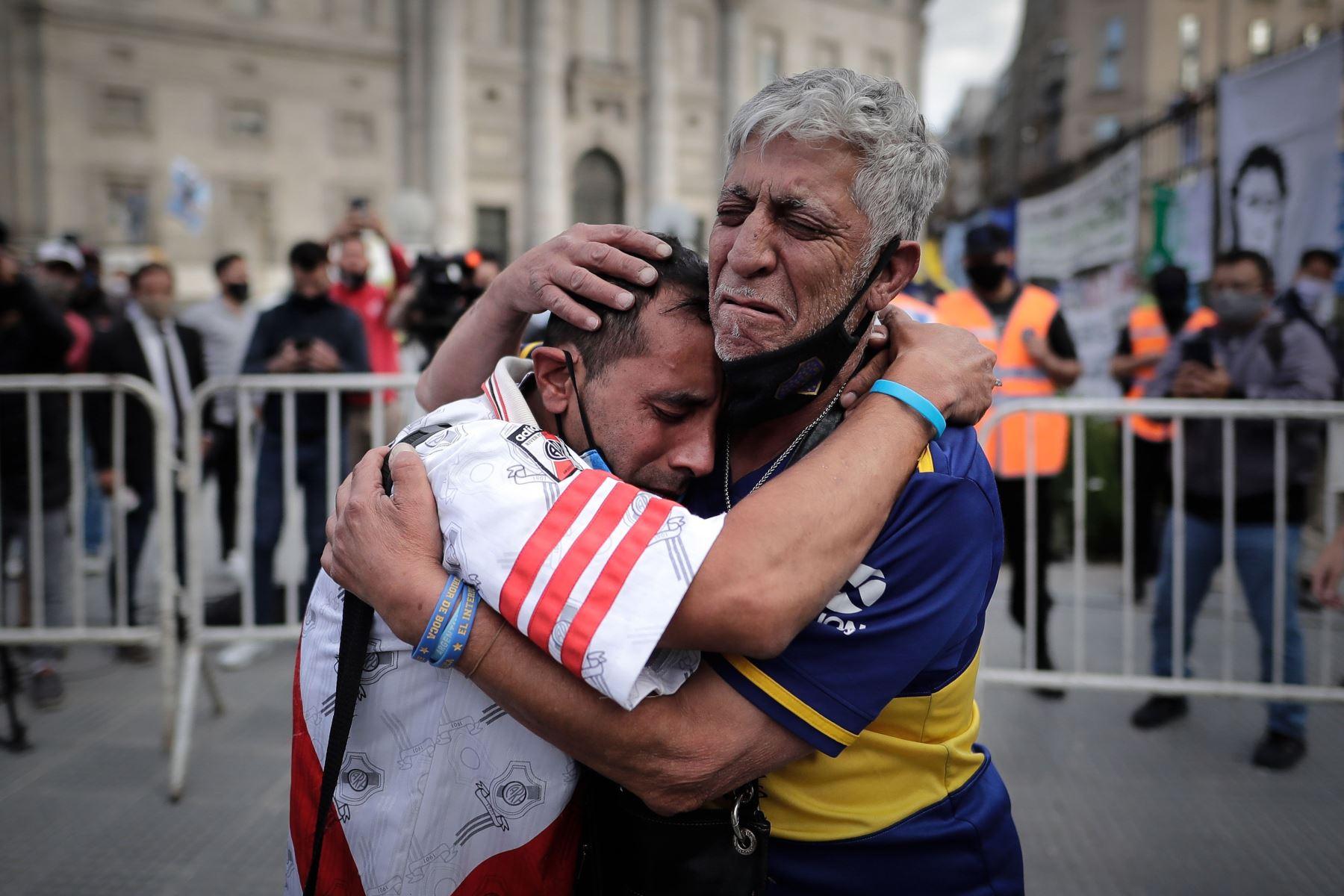 Un aficionado con la camiseta del Boca Juniors y otro con la camiseta del River Plate, se abrazan luego de despedir los restos de Diego Armando Maradona en el velatorio de la capital bonaerense, en la Plaza de Mayo. Foto: EFE