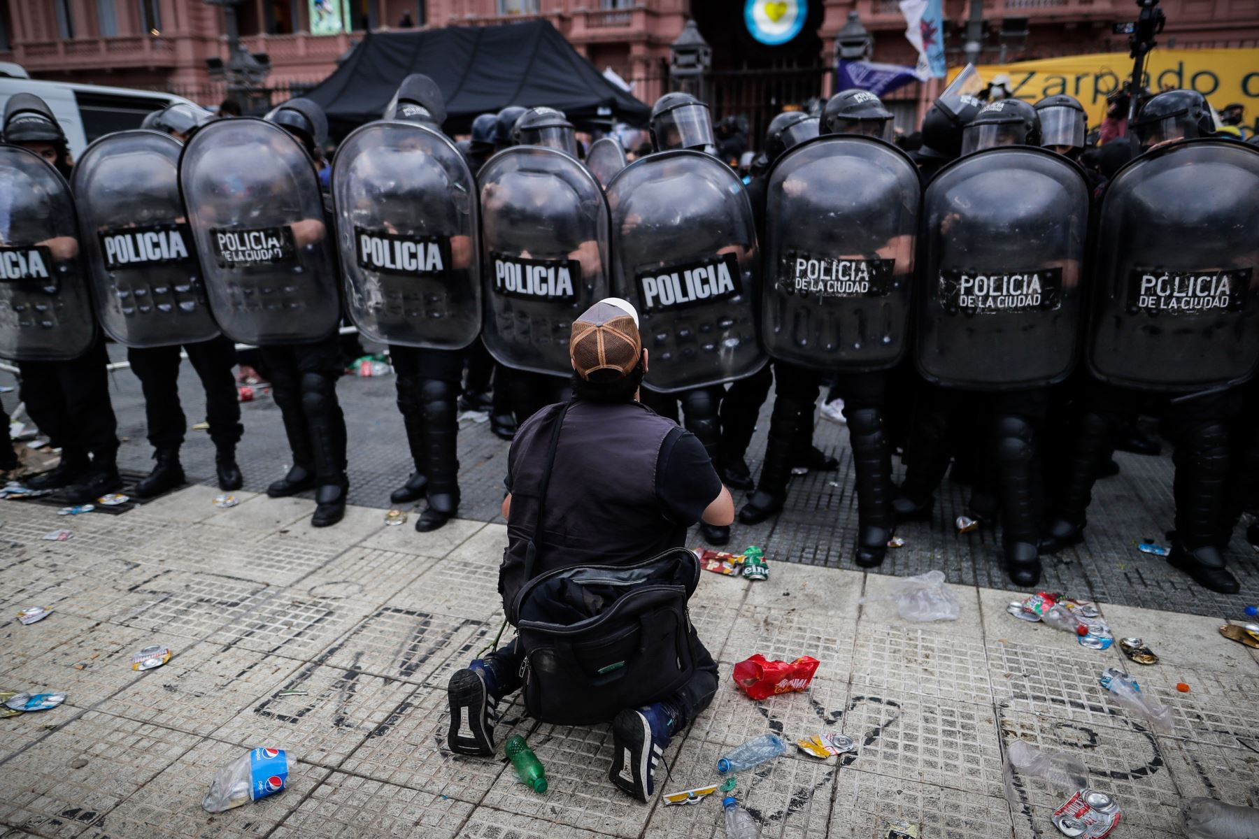 Una persona se arrodilla delante de la policía durante la espera para poder ingresar al velatorio de Diego Armando Maradona,  en la Plaza de Mayo de Buenos Aires. Foto: EFE