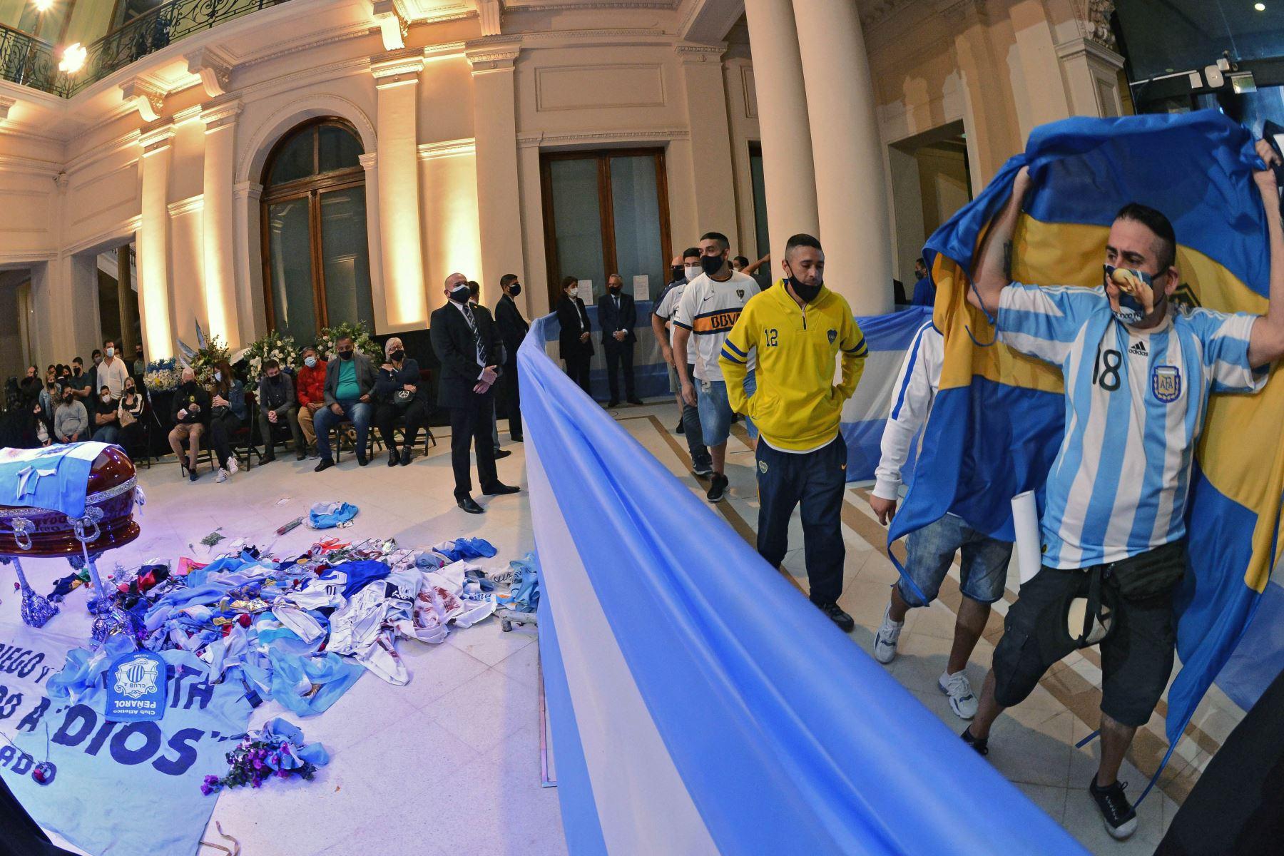 Hinchas que rinden homenaje al ataúd de la leyenda del fútbol argentino Diego Maradona en la capilla del palacio presidencial de la Casa Rosada en Buenos Aires. Foto: AFP