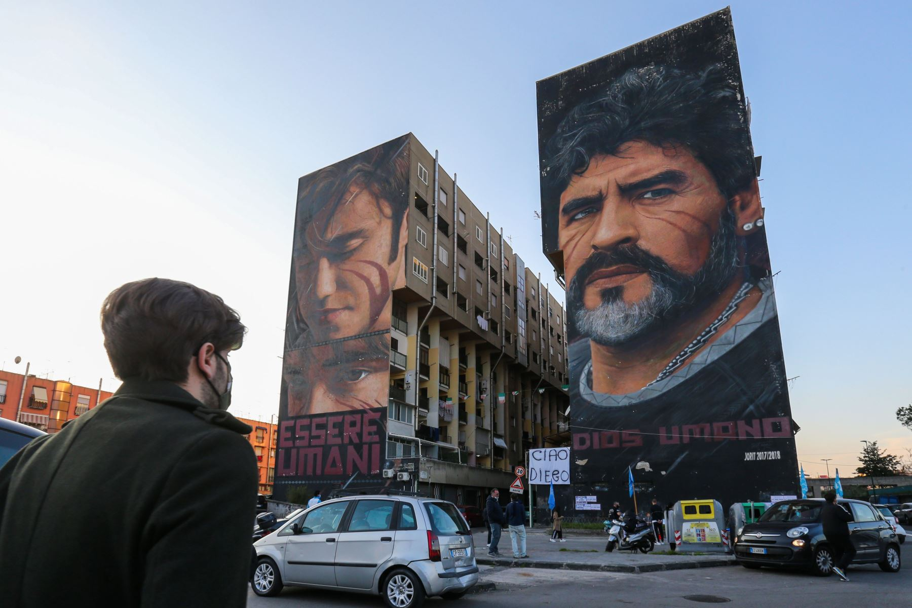"""La gente se reúne al pie de un mural de la leyenda del fútbol argentino Diego Maradona  en Nápoles, sur de Italia, para llorar su muerte. Maradona, ampliamente recordado por su gol """"Mano de Dios"""" contra Inglaterra en los cuartos de final del Mundial de 1986. Foto: AFP"""