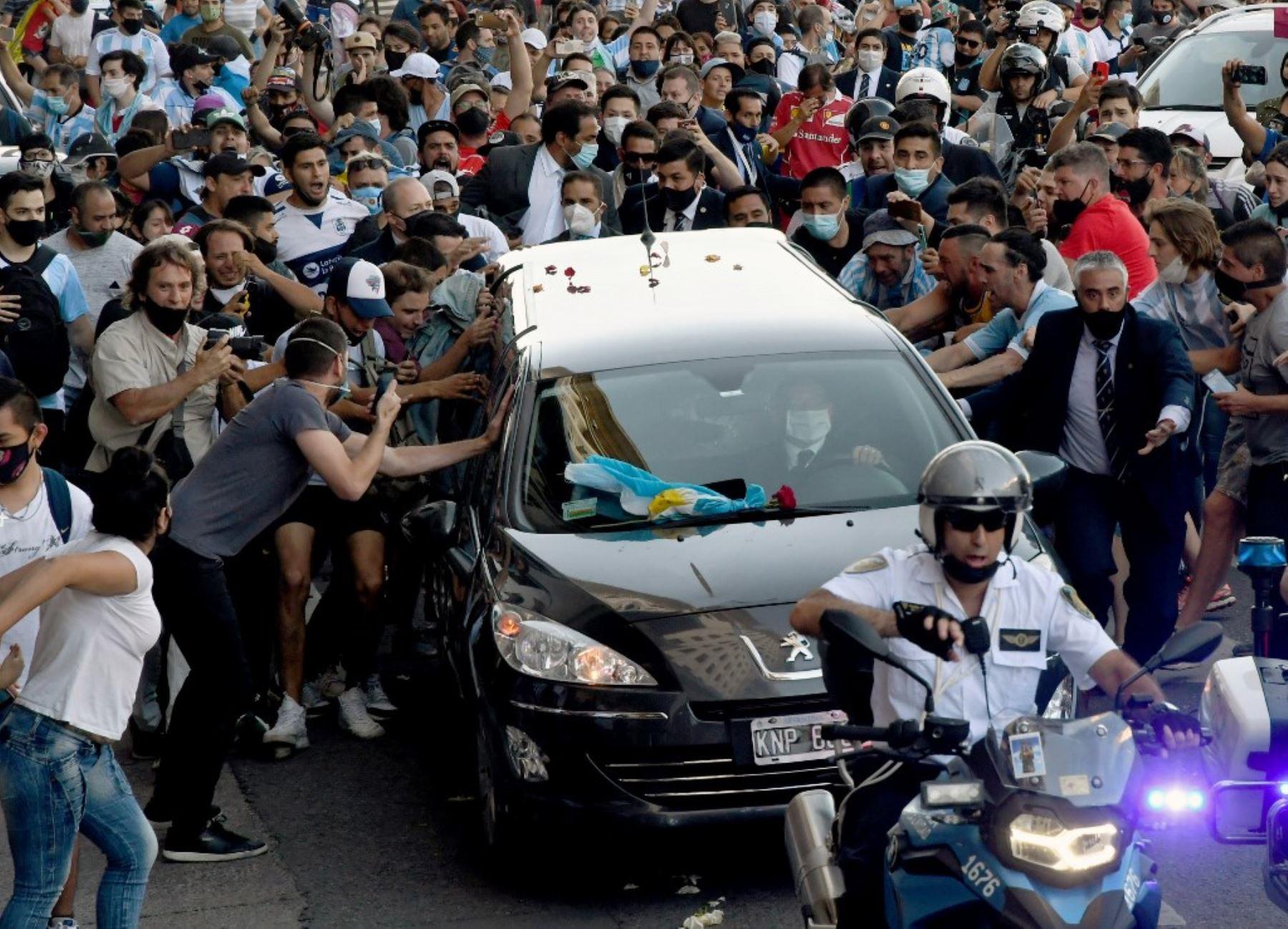 Fanáticos apiñados junto al coche fúnebre que transporta a la leyenda del fútbol argentino Diego Armando Maradona en su camino desde el palacio presidencial de la Casa Rosada al cementerio, en Buenos Aires. Foto: AFP