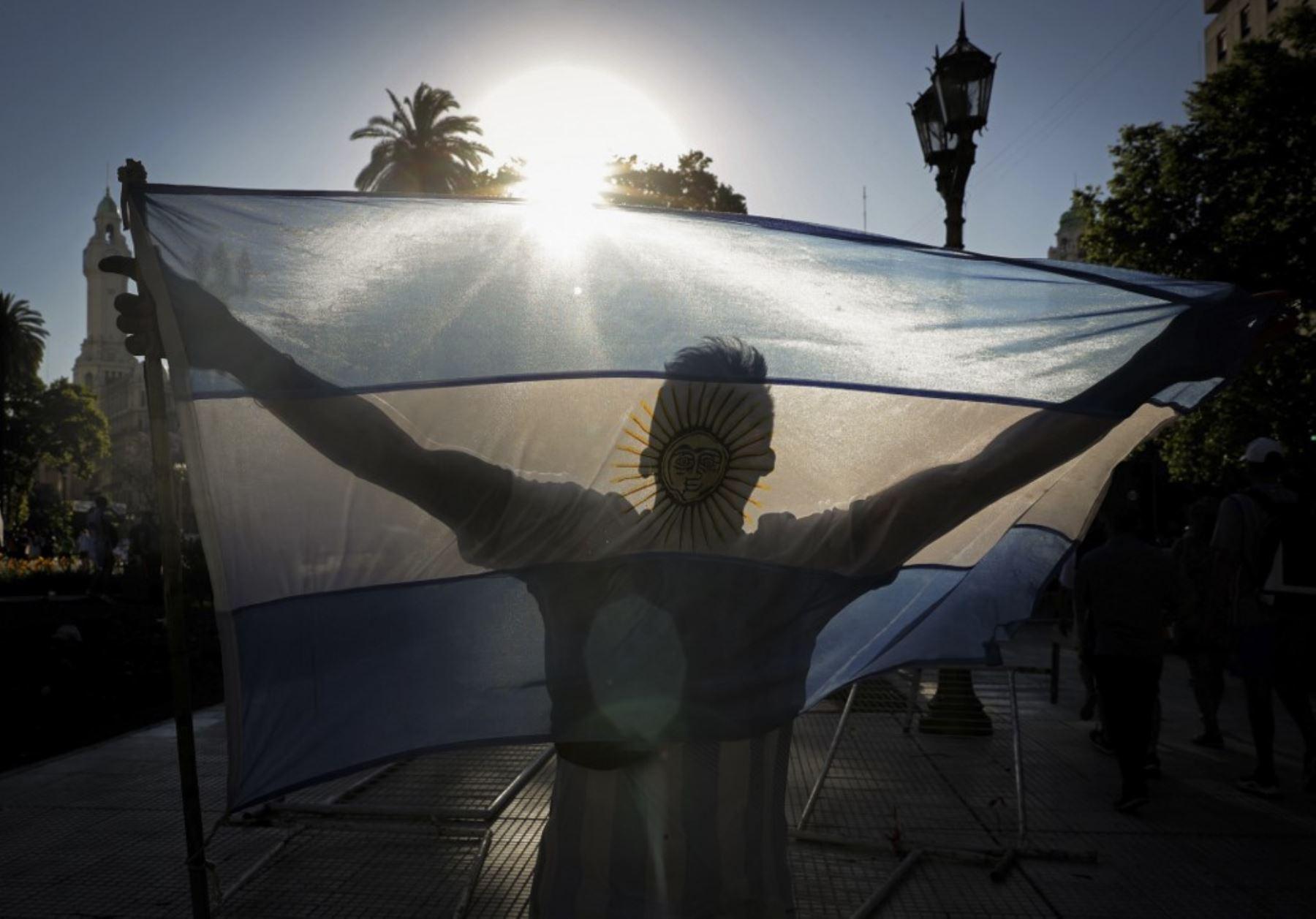 Un fanático de la leyenda del fútbol argentino Diego Armando Maradona sostiene una bandera argentina en la Plaza de Mayo frente al palacio presidencial Casa Rosada donde tuvo lugar el velorio de Maradona, en Buenos Aires. Foto: AFP