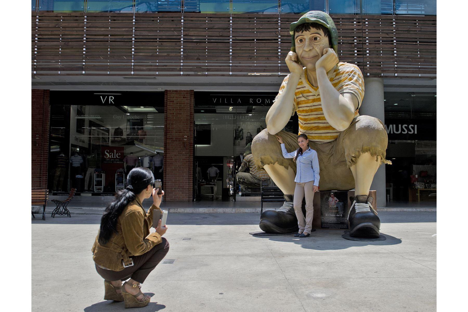 """Una mujer toma una fotografía de la escultura del famoso personaje de la televisión latinoamericana """"El Chavo del Ocho"""" exhibida en el Mall Chipichape, Colombia. Foto: AFP"""
