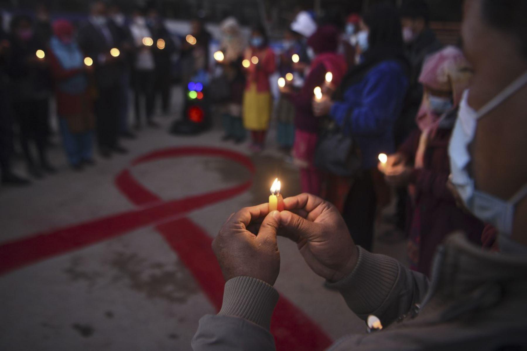 Los voluntarios encienden velas en forma de cinta roja durante un evento de sensibilización en la víspera del Día Mundial del SIDA, en Katmandú. Foto: AFP