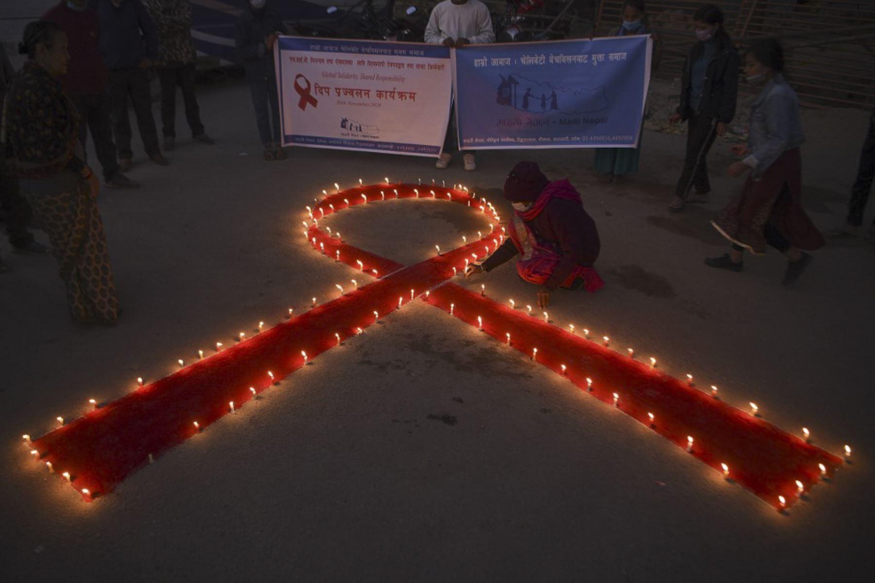 Un voluntario enciende velas en forma de lazo rojo durante un evento de sensibilización en la víspera del Día Mundial del SIDA, en Katmandú. Foto: AFP