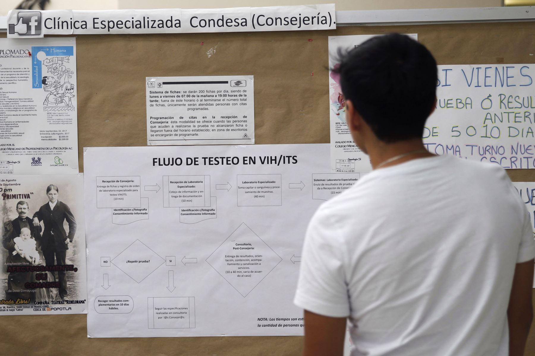 Un hombre mientras observa un cartel informativo, en la clínica especializada VIH Condesa, en Ciudad de México (México). Los pacientes mexicanos que padecen VIH viven pendientes de un hilo por la falta de medicamentos antirretrovirales, la suspensión de consultas y el miedo a infectarse del nuevo virus de la covid-19. Foto: EFE