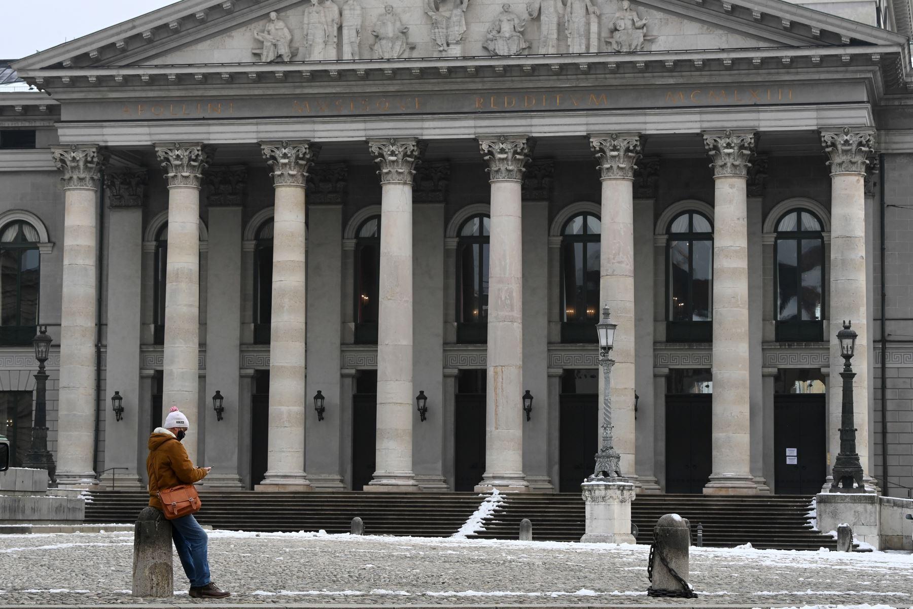 Un hombre con una máscara facial revisa su teléfono en la plaza vacía frente a la ópera de Múnich, en el sur de Alemania, en medio de la pandemia del nuevo coronavirus Covid-19 en curso. Foto: AFP