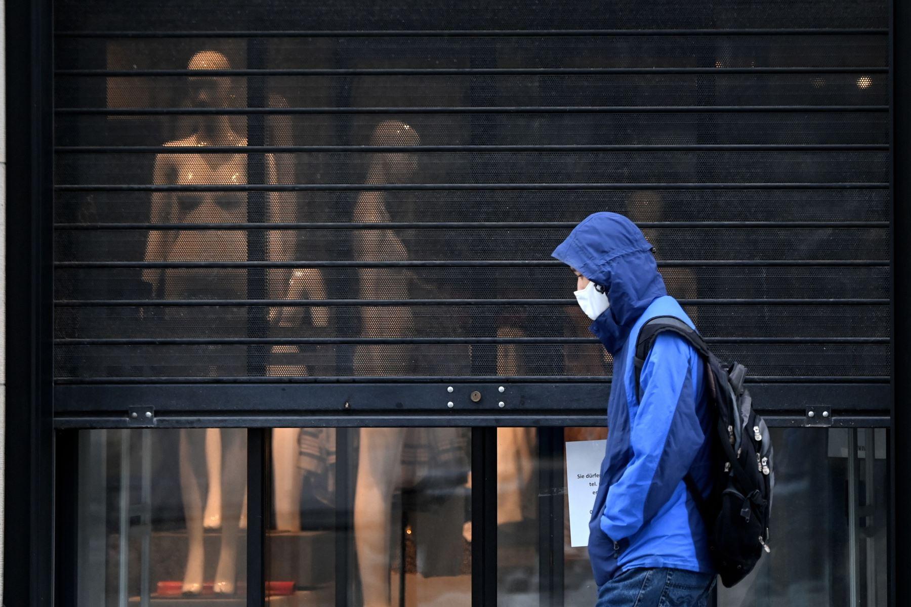 Un peatón con una máscara facial camina frente a una tienda de moda cerrada en la ciudad de Múnich, en el sur de Alemania, en medio de la pandemia del nuevo coronavirus Covid-19 en curso. Foto: AFP