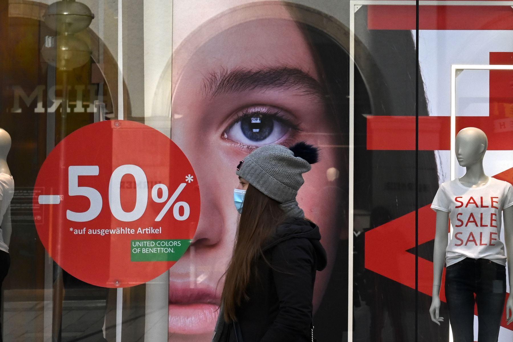 Una mujer con una máscara facial camina frente a una tienda de moda cerrada con ventas anunciadas en sus escaparates, en la ciudad de Múnich, en el sur de Alemania, en medio de la pandemia del nuevo coronavirus Covid-19 en curso. Foto: AFP