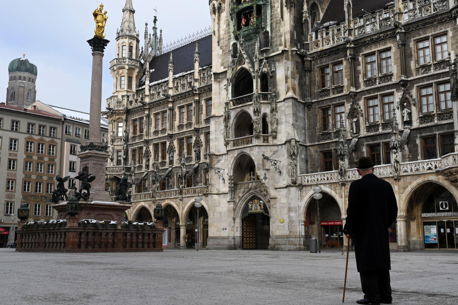 Un hombre vestido de negro con un bastón y un sombrero se encuentra en la plaza Marienplatz vacía frente al ayuntamiento en el centro de la ciudad de Múnich, en el sur de Alemania, en medio de la pandemia del nuevo coronavirus Covid-19 en curso. Foto: AFP