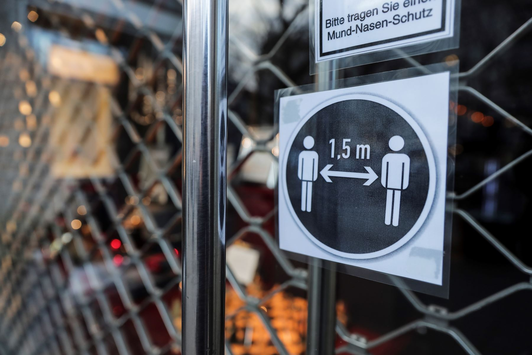 Un cartel, indica mantener una distancia de 1,5 metros en la puerta de entrada de una tienda cerrada en Berlín, Alemania. Foto: EFE