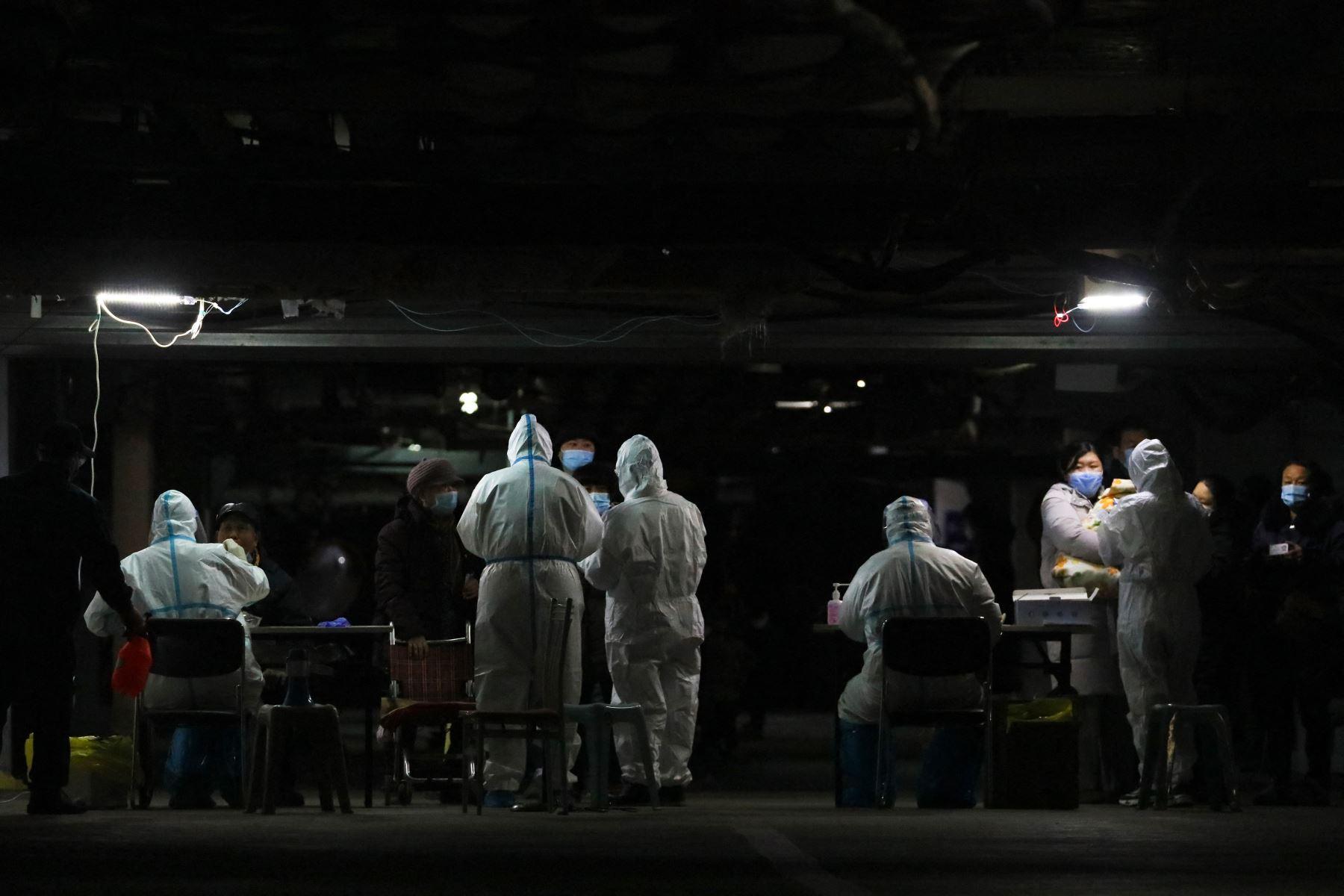 Los residentes se someten a pruebas de Covid-19 en el sótano de un complejo residencial como parte de un programa de pruebas masivas tras los nuevos casos del virus que surgieron en Shijiazhuang, en la provincia de Hebei, en el centro de China, el 12 de enero de 2021. Foto: AFP