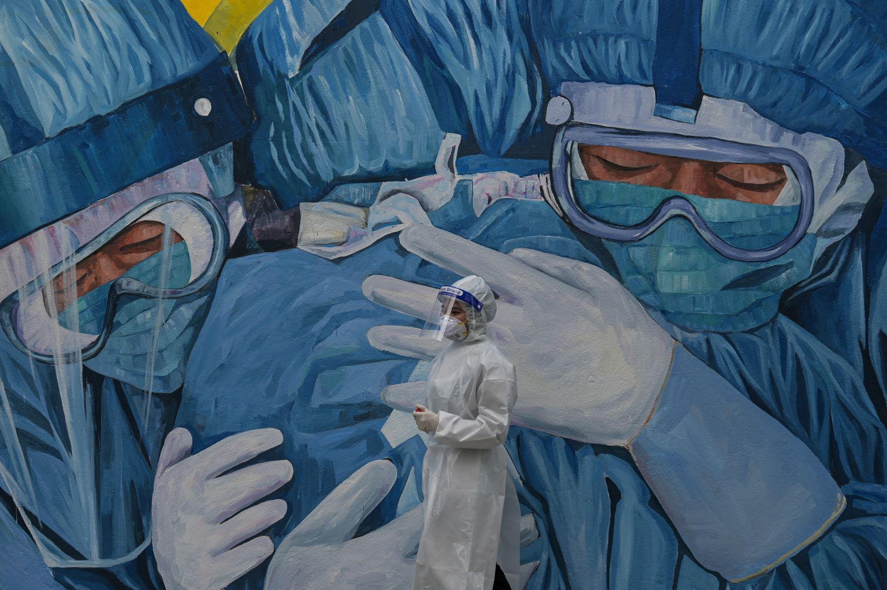 Un personal médico con un traje de protección espera en el centro de pruebas de detección Covid-19 en la Clínica Privada Ajwa en Shah Alam en las afueras de Kuala Lumpur un 12 de enero de 2021, mientras el rey de Malasia declaró un estado de emergencia nacional para combatir la nueva ola de coronavirus. (Foto: AFP)
