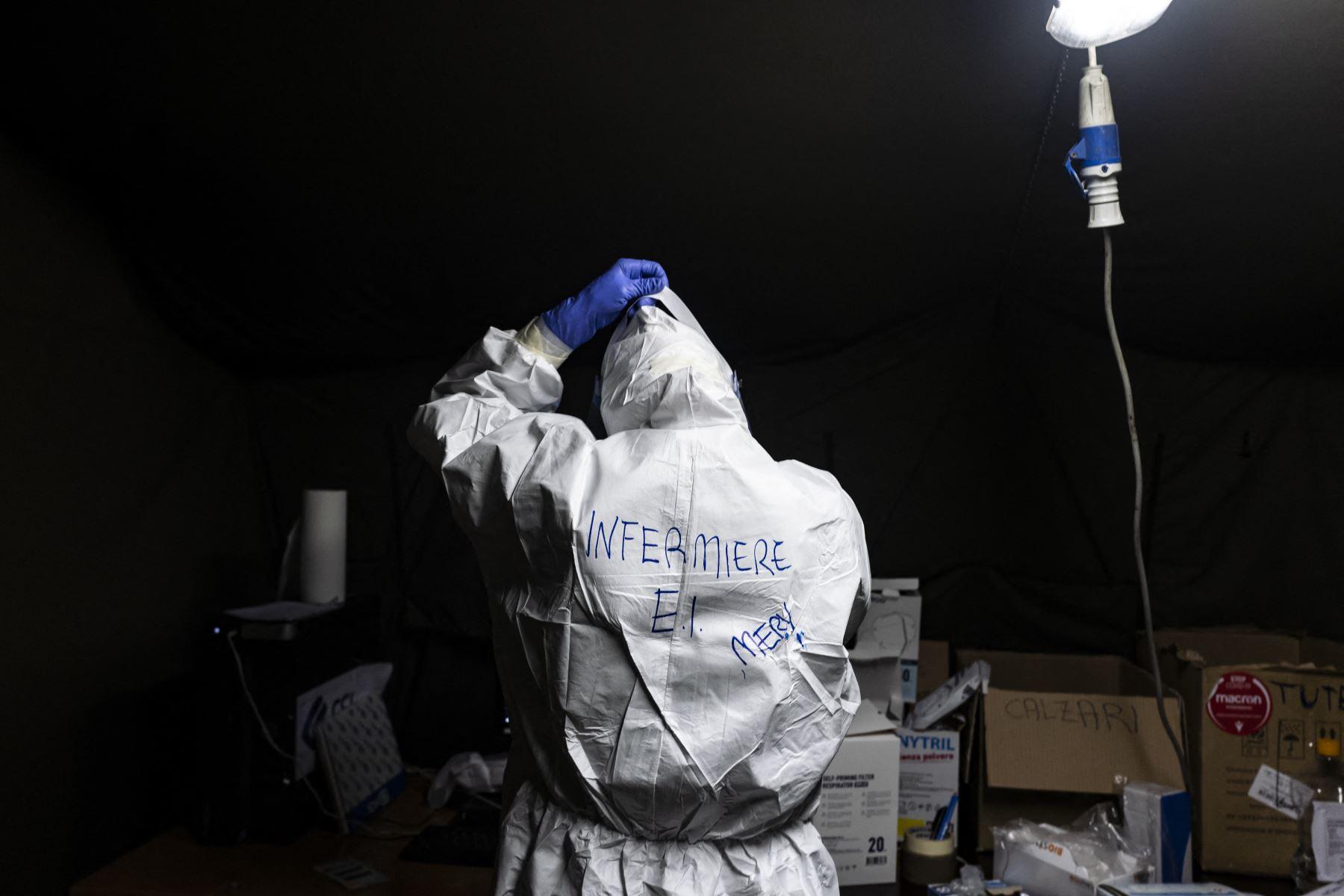 Una trabajadora médica ajusta su traje de protección en un centro de pruebas para COVID-19 instalado por el Ejército italiano en el estacionamiento del estadio de la Juventus en Turín. Italia ha sido uno de los países más afectados por la pandemia Covid-19, con más de 75.000 muertes hasta ahora. Foto: AFP