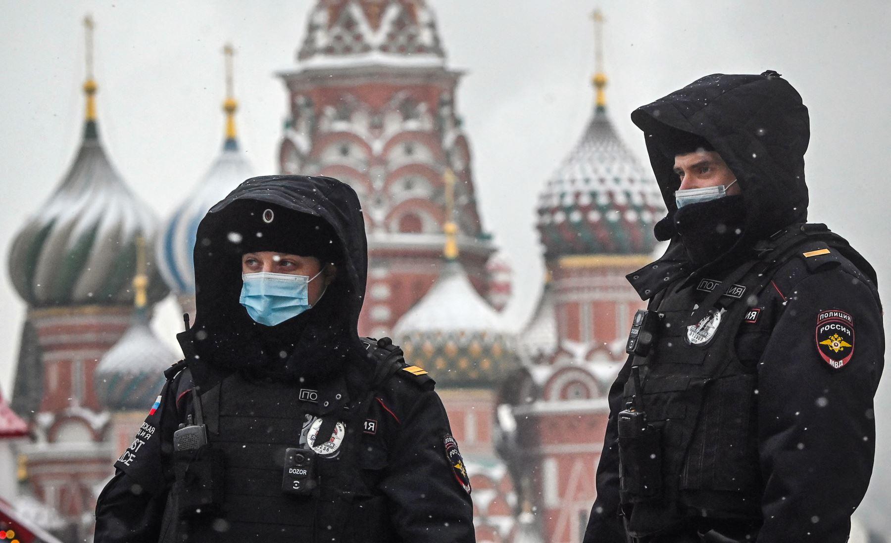 Agentes de policía rusos con mascarillas caminan por la Plaza Roja frente a la catedral de San Basilio en el centro de Moscú, en medio de la crisis relacionada con la pandemia Covid-19 causada por el nuevo coronavirus. - Rusia confirmó 22,934 nuevos casos diarios de Covid-19, incluidos 5,001 en Moscú. Foto: AFP
