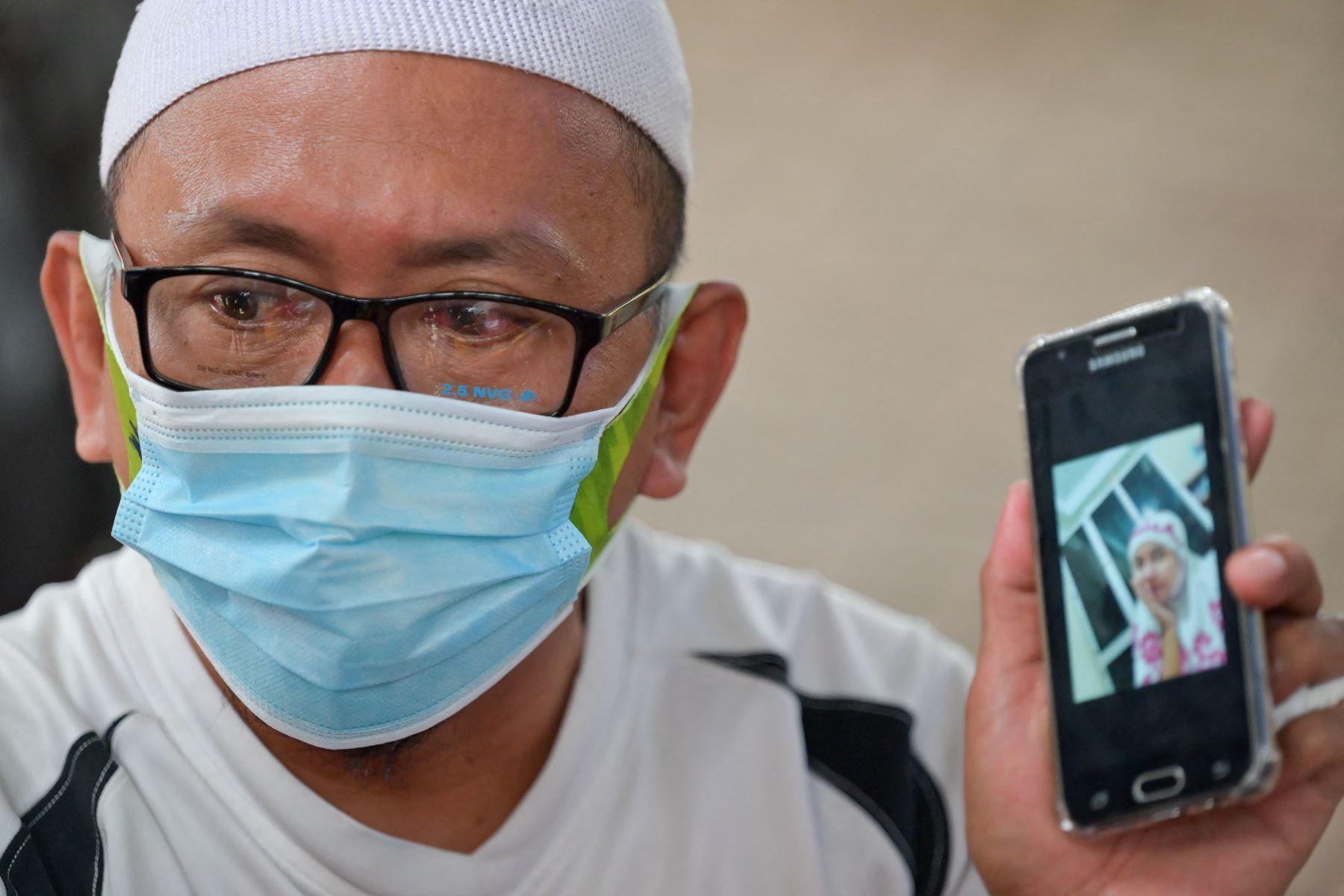 Rafik Al-Idrus muestra una foto de su esposa, una de las 62 personas a bordo del vuelo SJ182 de Sriwijaya Air que se estrelló poco después del despegue el 9 de enero. Foto: AFP