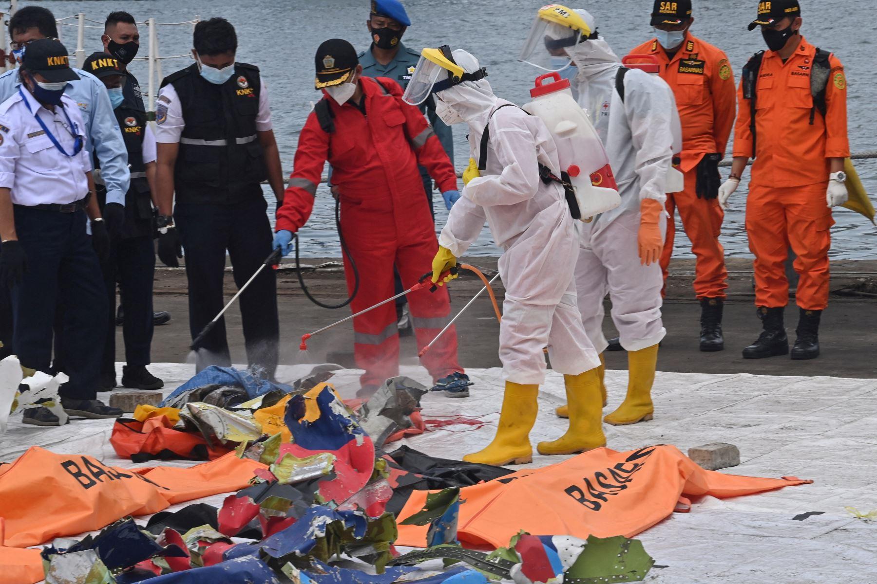 Miembros de la Cruz Roja Indonesia rocían desinfectante sobre artículos recuperados del vuelo SJ182 de Sriwijaya Air en el puerto de Tanjung Priok. Foto: AFP