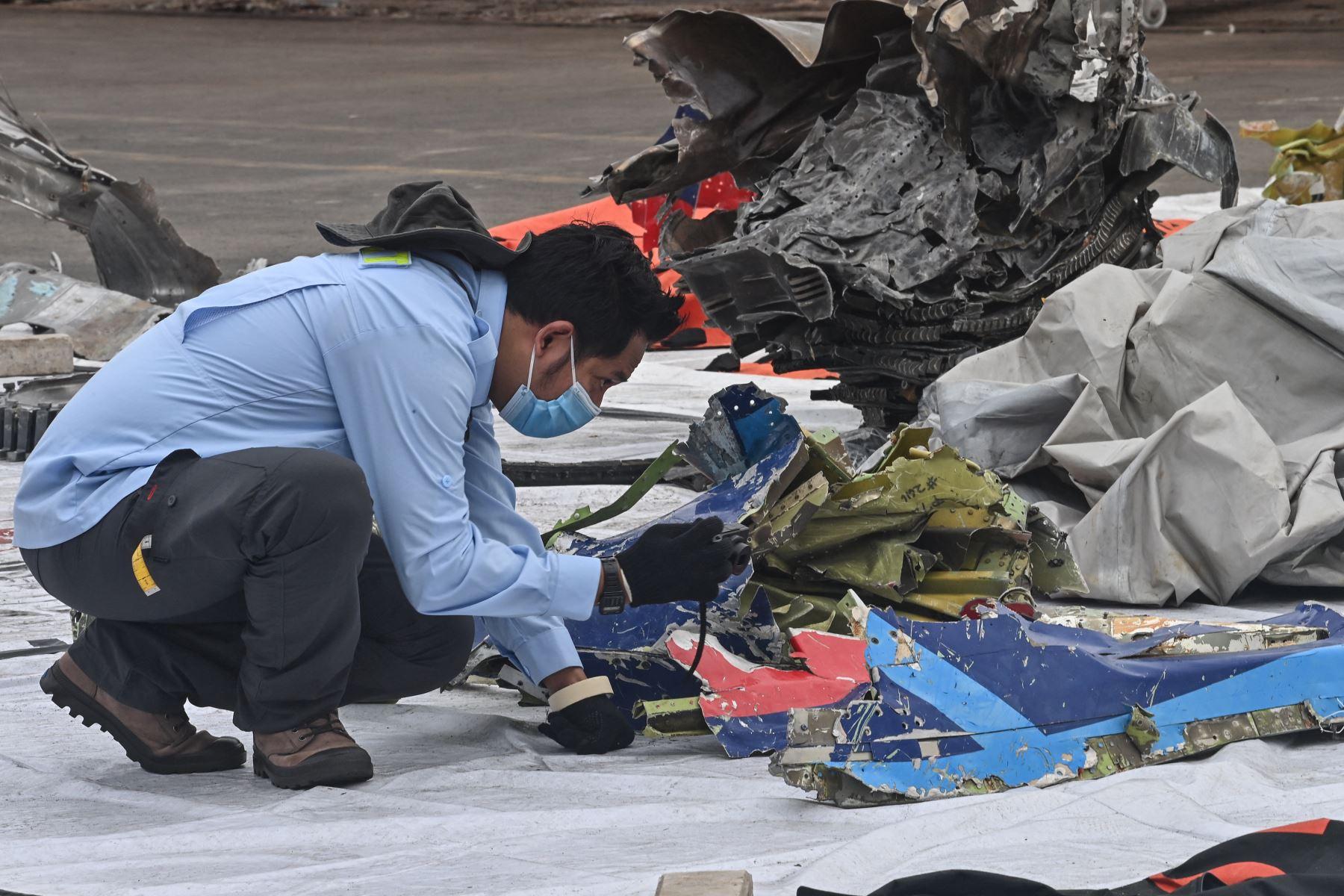 Un miembro del Comité Nacional de Seguridad del Transporte (KNKT) inspecciona los restos del vuelo SJ182 de Sriwijaya Air en el puerto de Tanjung Priok. Foto: AFP