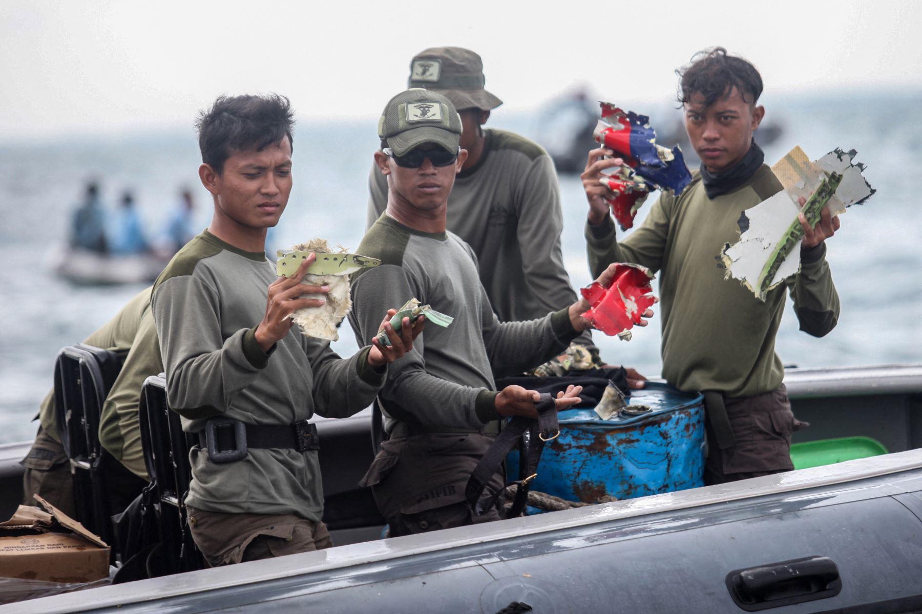 Buzos de la Armada de Indonesia muestran piezas de escombros recuperados frente a la costa norte de Yakarta. Foto: AFP