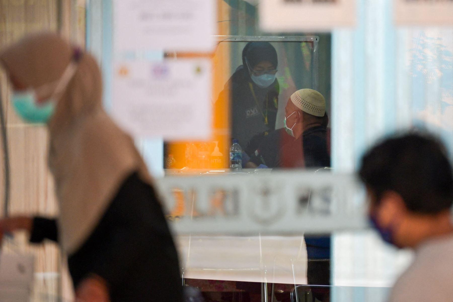 Un familiar de una de las 62 personas a bordo del vuelo SJ182 de Sriwijaya Air, que se estrelló poco después del despegue el 9 de enero, visita un hospital policial para realizar una prueba de ADN en Yakarta. Foto: AFP