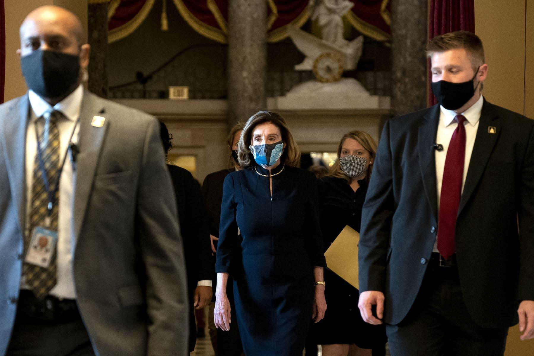 La presidenta de la Cámara de Representantes, Nancy Pelosi, usa una máscara protectora mientras camina hacia el piso de la Cámara durante una votación sobre la acusación del presidente Donald Trump en el Capitolio de los Estados Unidos Foto: AFP