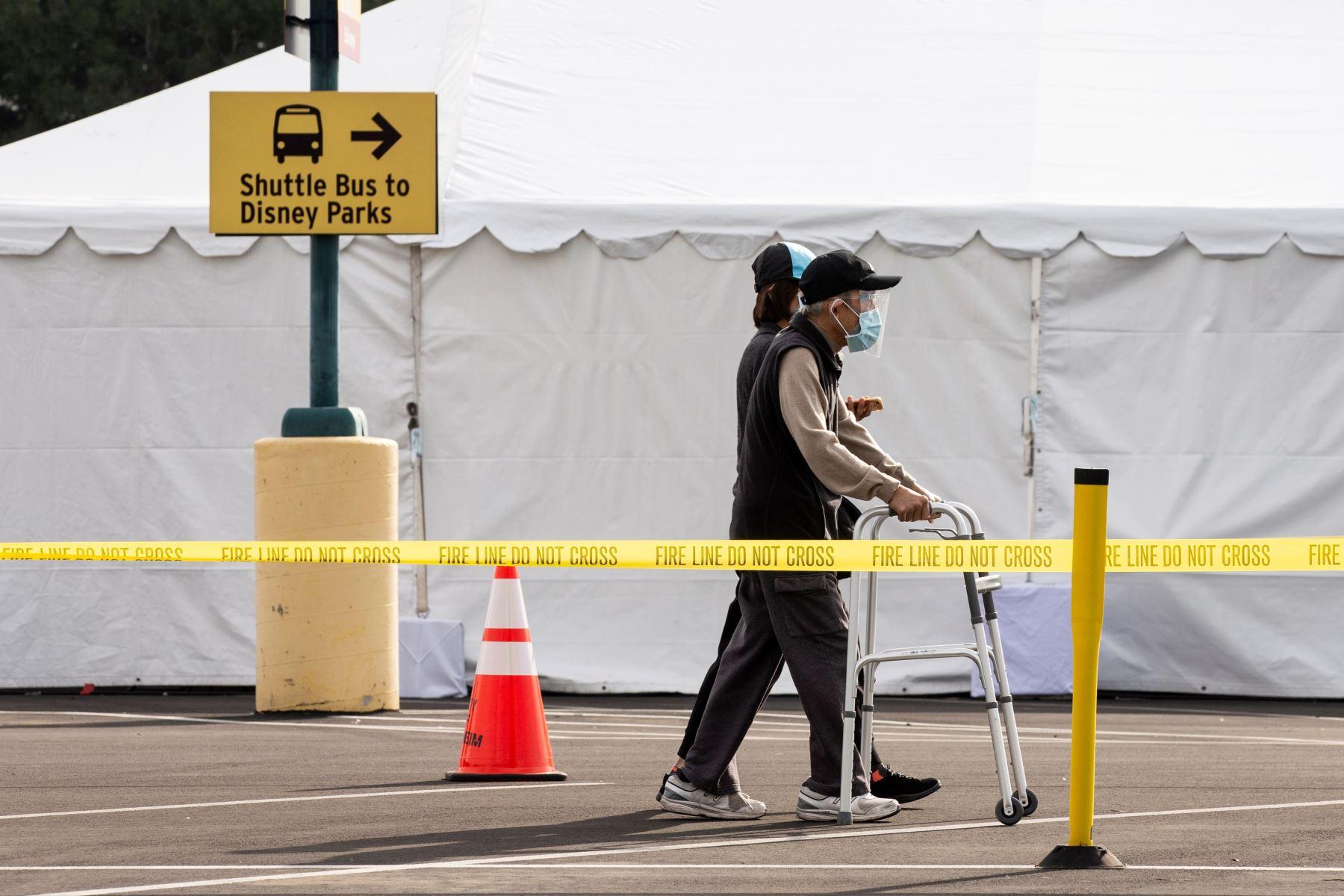 Las personas se van después de recibir la vacuna covid-19 en un estacionamiento de Disneyland en Anaheim, California. Foto: EFE