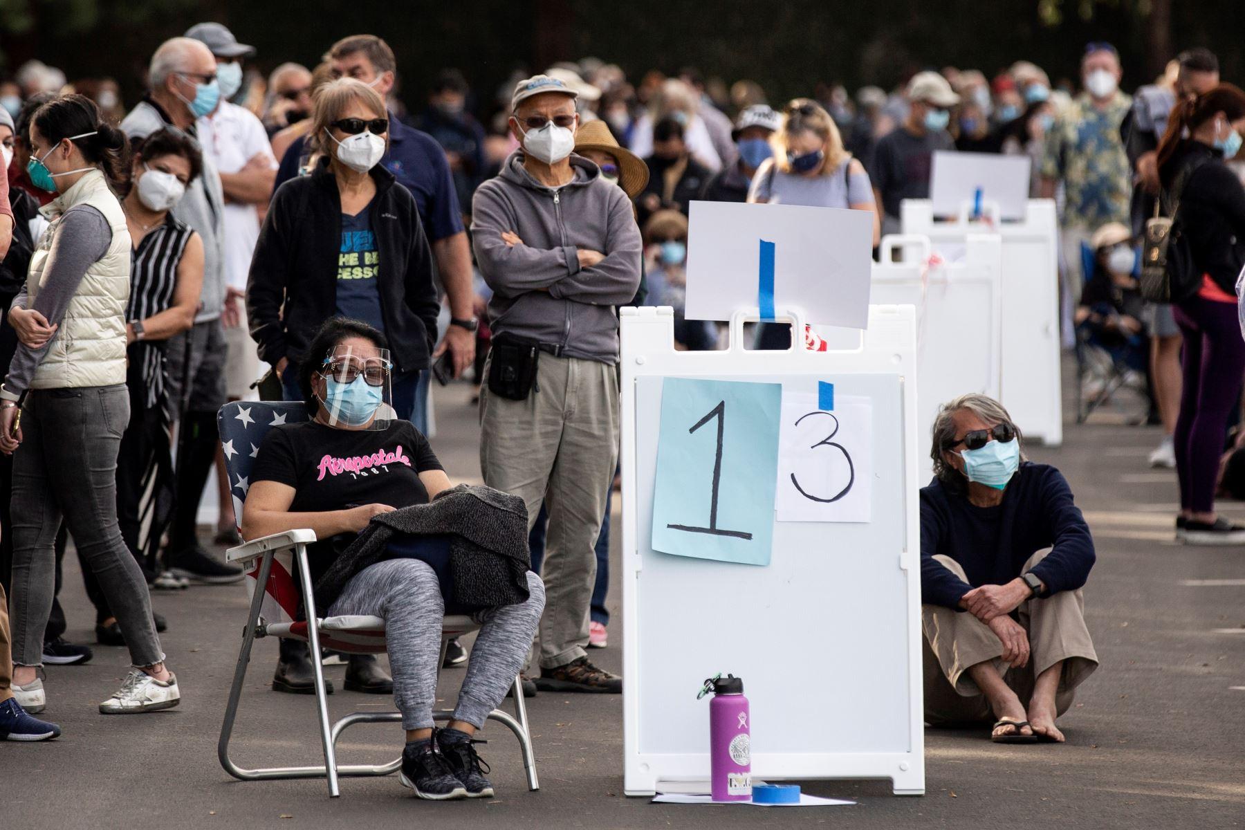 Personas hacen cola mientras esperan vacunarse contra covid-19 en un estacionamiento de Disneyland en Anaheim, California. Foto: EFE
