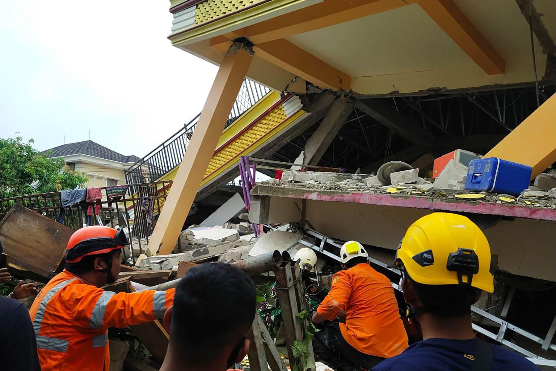 Rescatistas buscan sobrevivientes atrapados en un edificio derrumbado en Mamuju, después de que un terremoto de magnitud 6.2 sacudiera la isla de Sulawesi. Foto: AFP