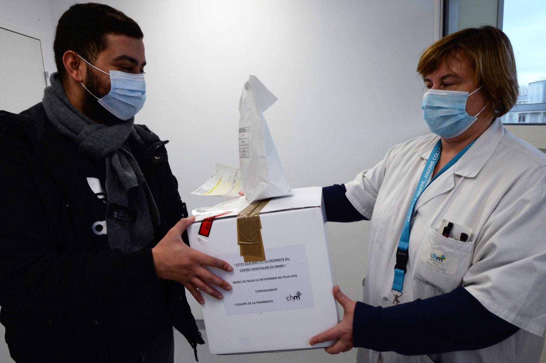 Un mensajero recoge una hielera que contiene kits para la vacuna Pfizer / BioNTech Covid-19, en la farmacia del Centro Hospitalario de Le Mans, en el oeste de Francia. Foto: AFP