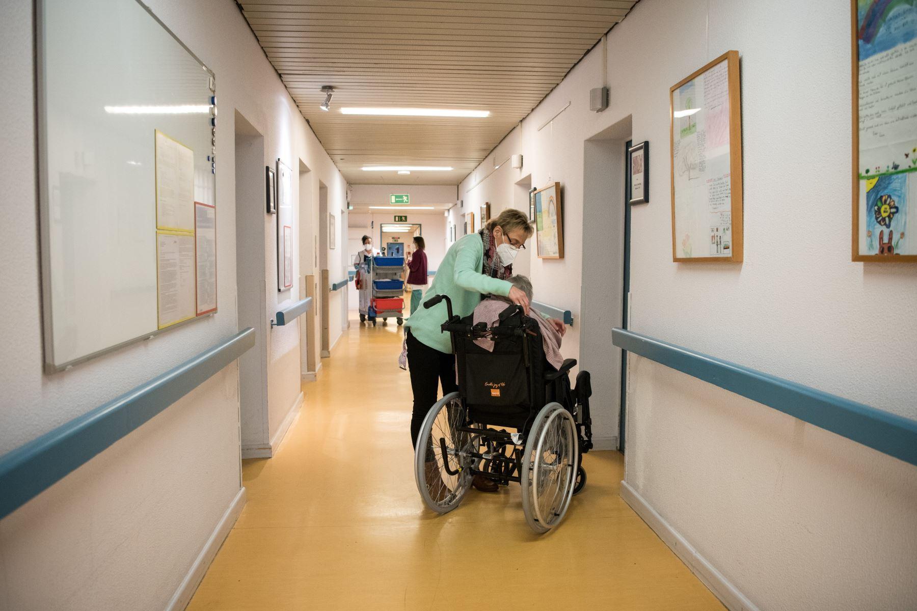 Una enfermera con una mascarilla protectora cuida a un residente en silla de ruedas en un hogar de ancianos en Berlín. Foto : AFP