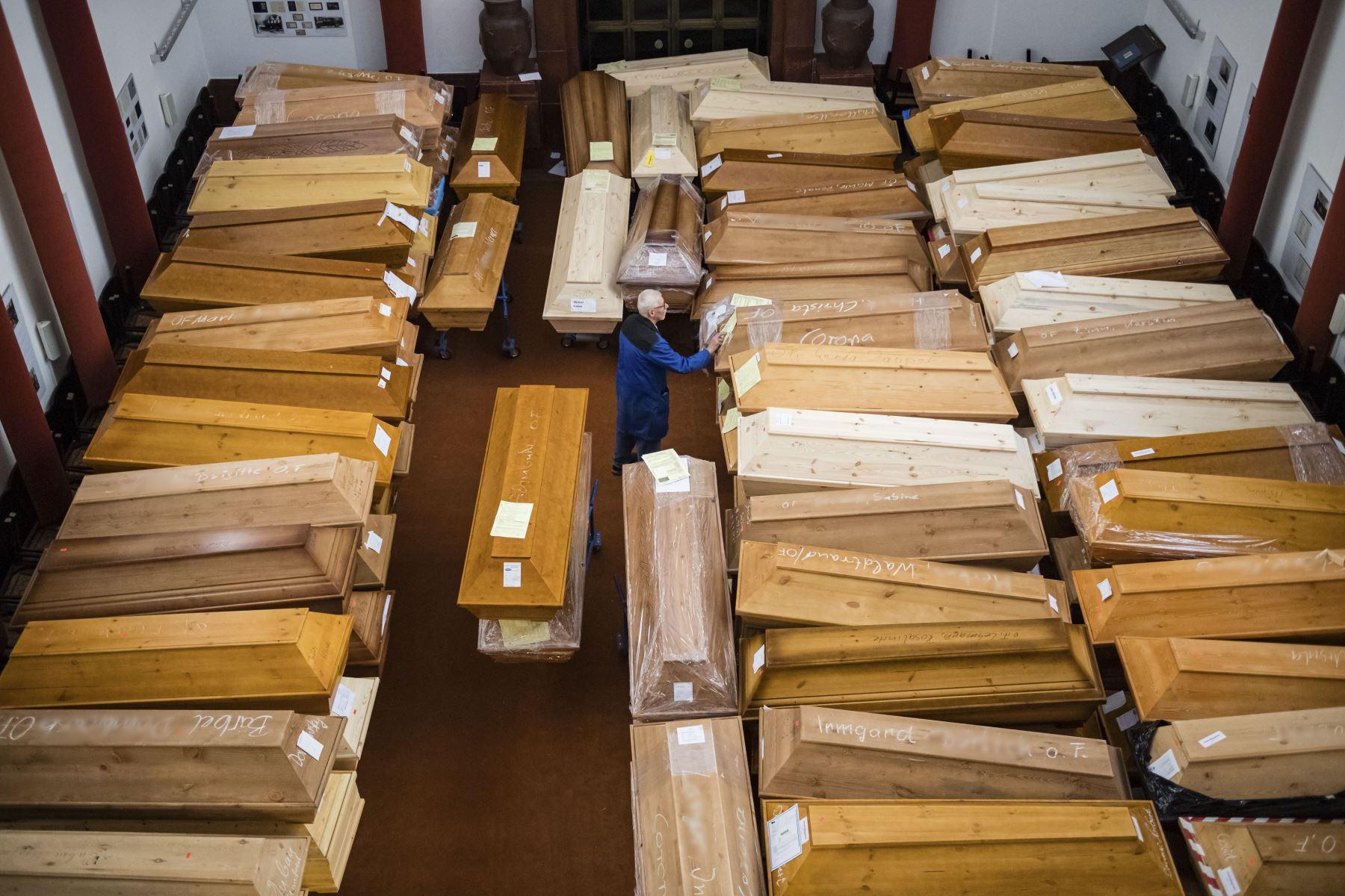 """Un empleado mueve ataúdes, algunos marcados con """"riesgo de infección"""" mientras que otros tienen """"corona"""" garabateada con tiza, en la sala de duelo del crematorio en Meissen, Alemania oriental. Foto: EFE"""