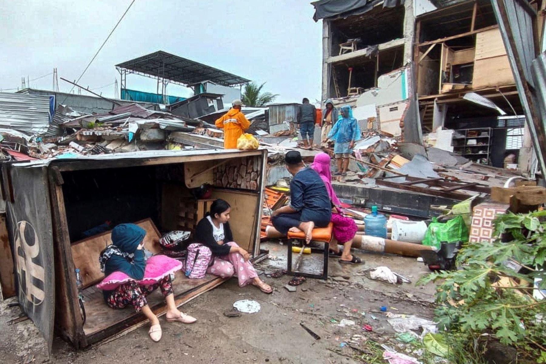 Personas sentadas dentro de una caja de madera frente a casas derrumbadas tras un terremoto de magnitud 6,2 en Mamuju, West Sulawesi, Indonesia, Al menos 42 personas murieron y decenas más resultaron heridas después de que un terremoto de 6.2 sacudiera la isla de Sulawesi.   Foto: EFE