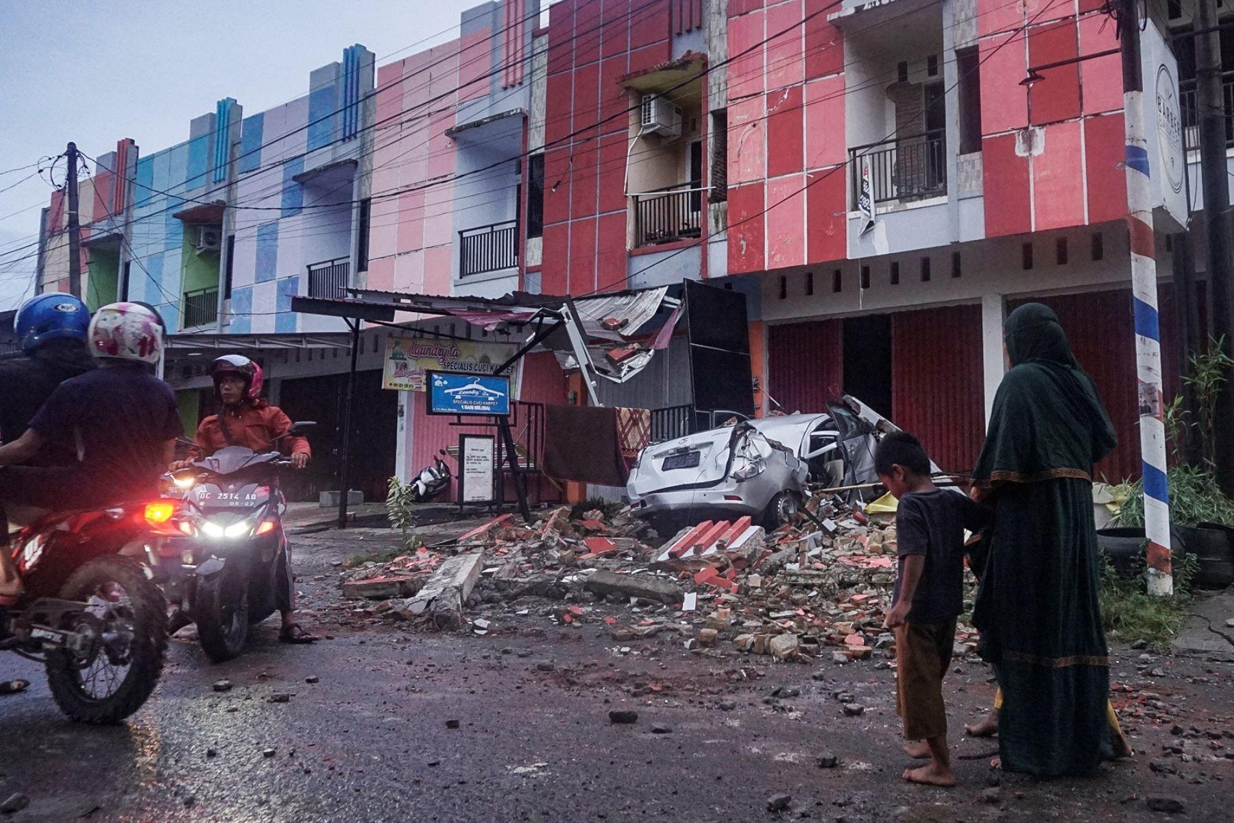 La gente pasa junto a un coche averiado tras el terremoto de magnitud 6,2 en Mamuju, West Sulawesi, Indonesia, Al menos 42 personas murieron y decenas más resultaron heridas tras un terremoto de 6,2. Isla de Sulawesi.  Foto:  EFE